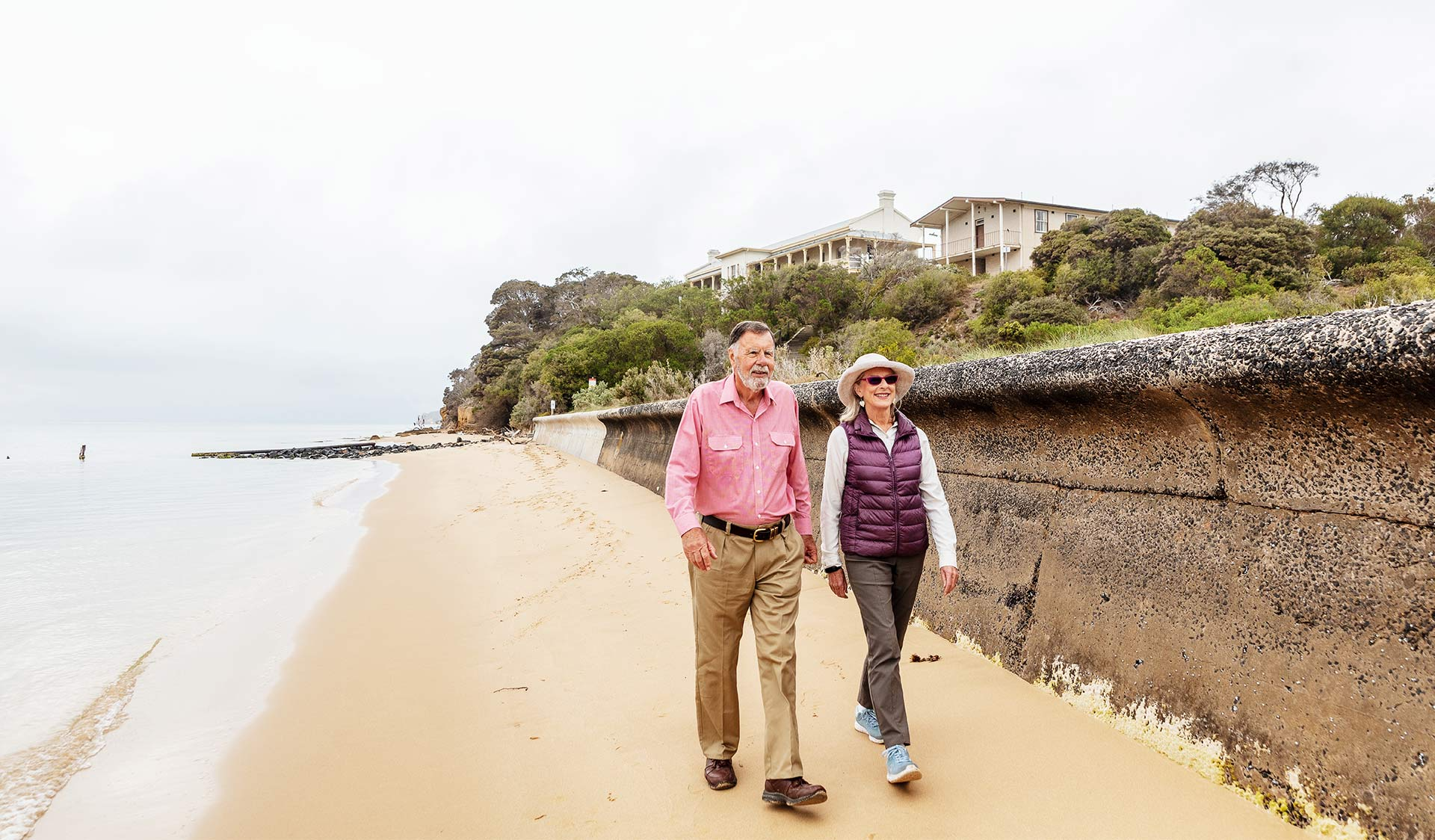An elderly couple walking along the beach together at the Quarantine Station in Point Nepean National Park