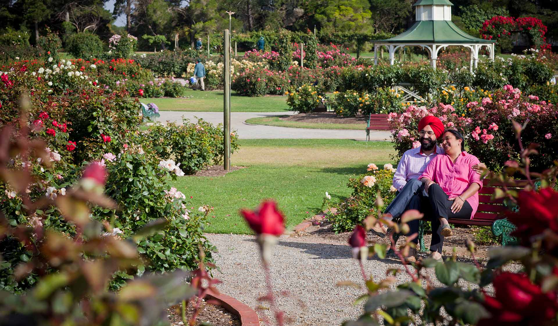 A couple sit on a bench in the rose garden at Werribee Park.