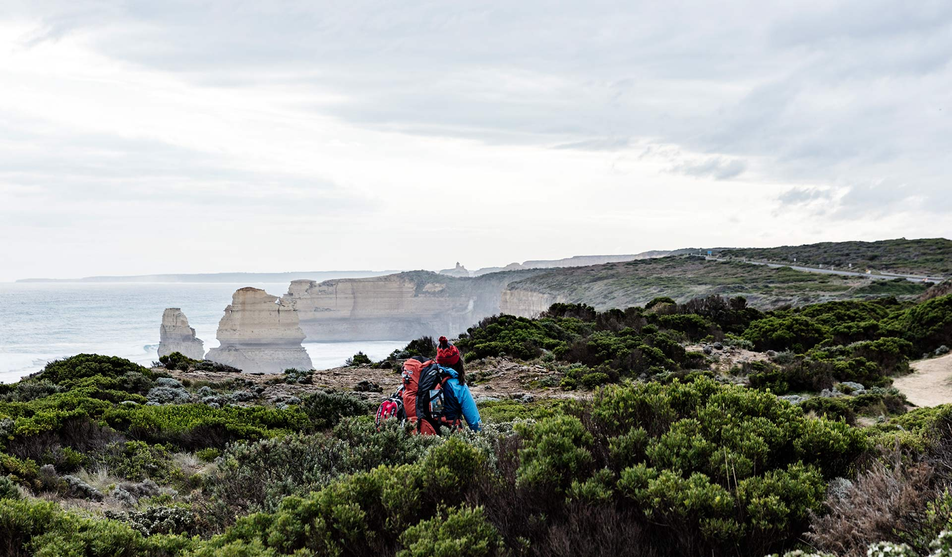 A women in a blue jacket walks through the heath on the cliffs above the Twelve Apostles.