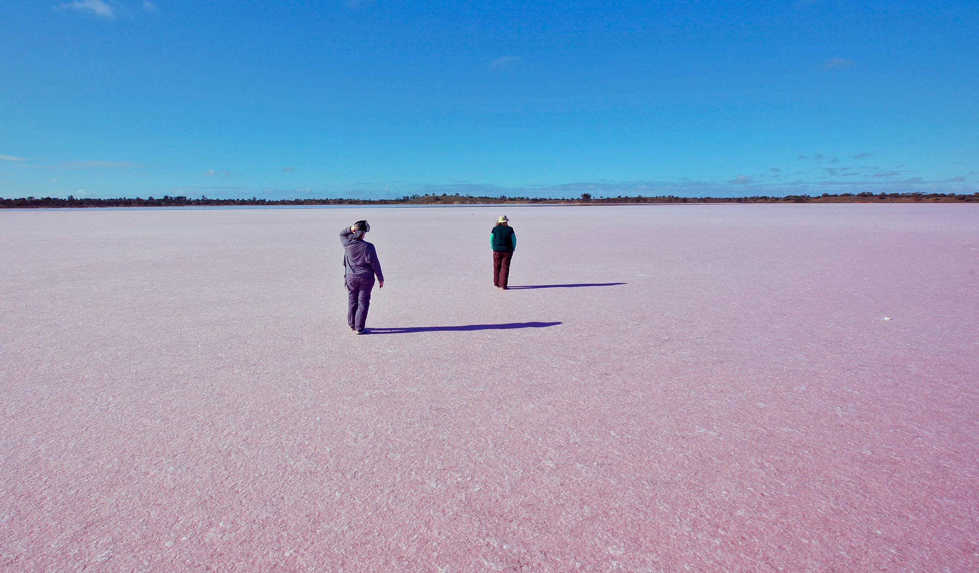 Two people walk across a dry pink salt lake.