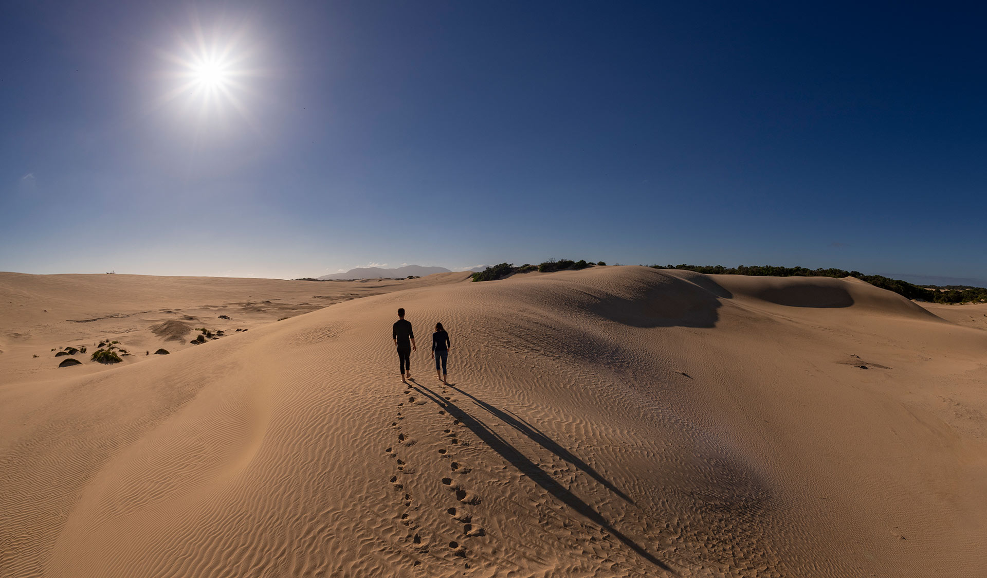 A man and woman walk along the top of an enourmous sand dune in the northern part of Wilsons Promontory.