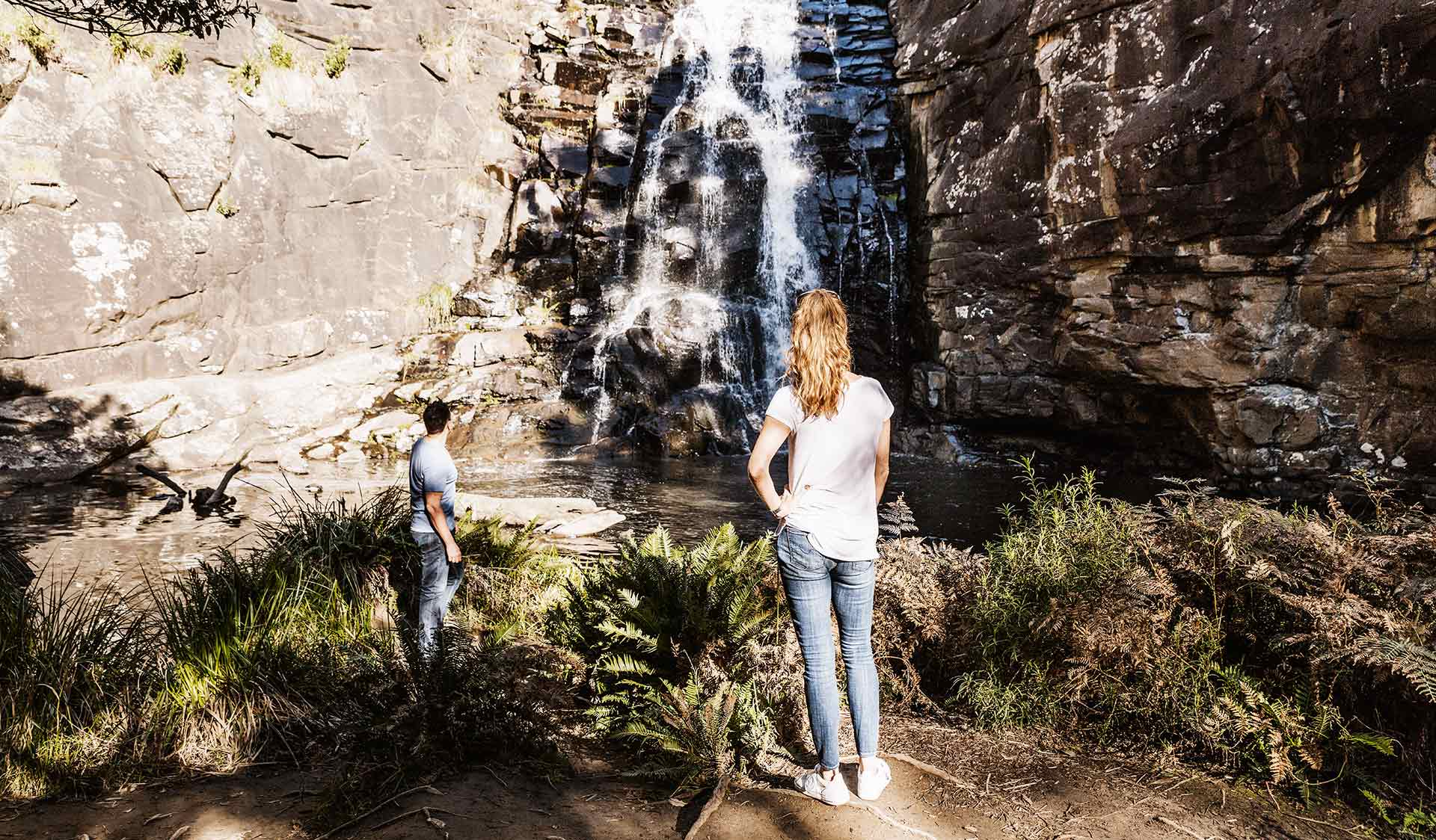A couple stand and admire Sheoak Falls near Lorne in the Great Otway National Park.