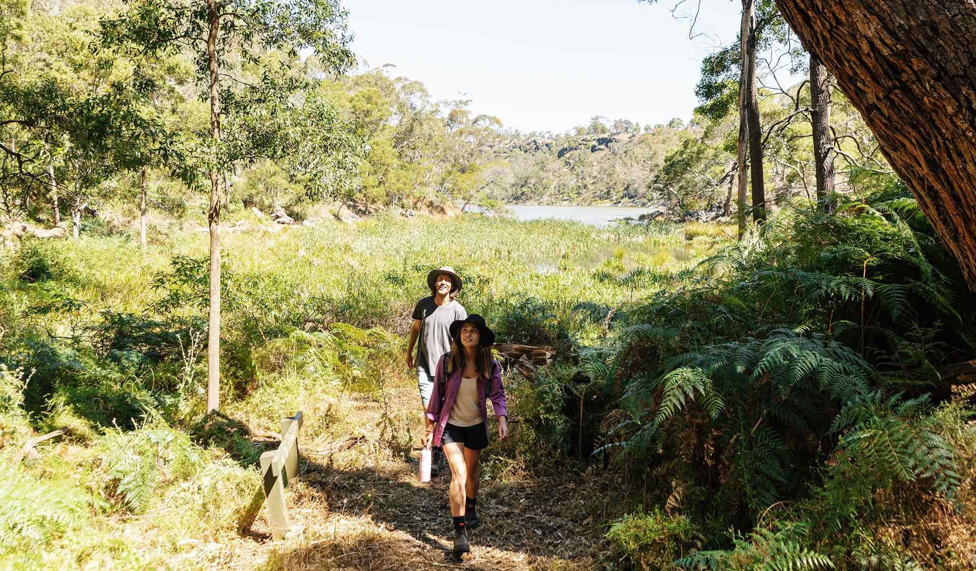 A young woman leading a man on a walk through Budj Bim National Park