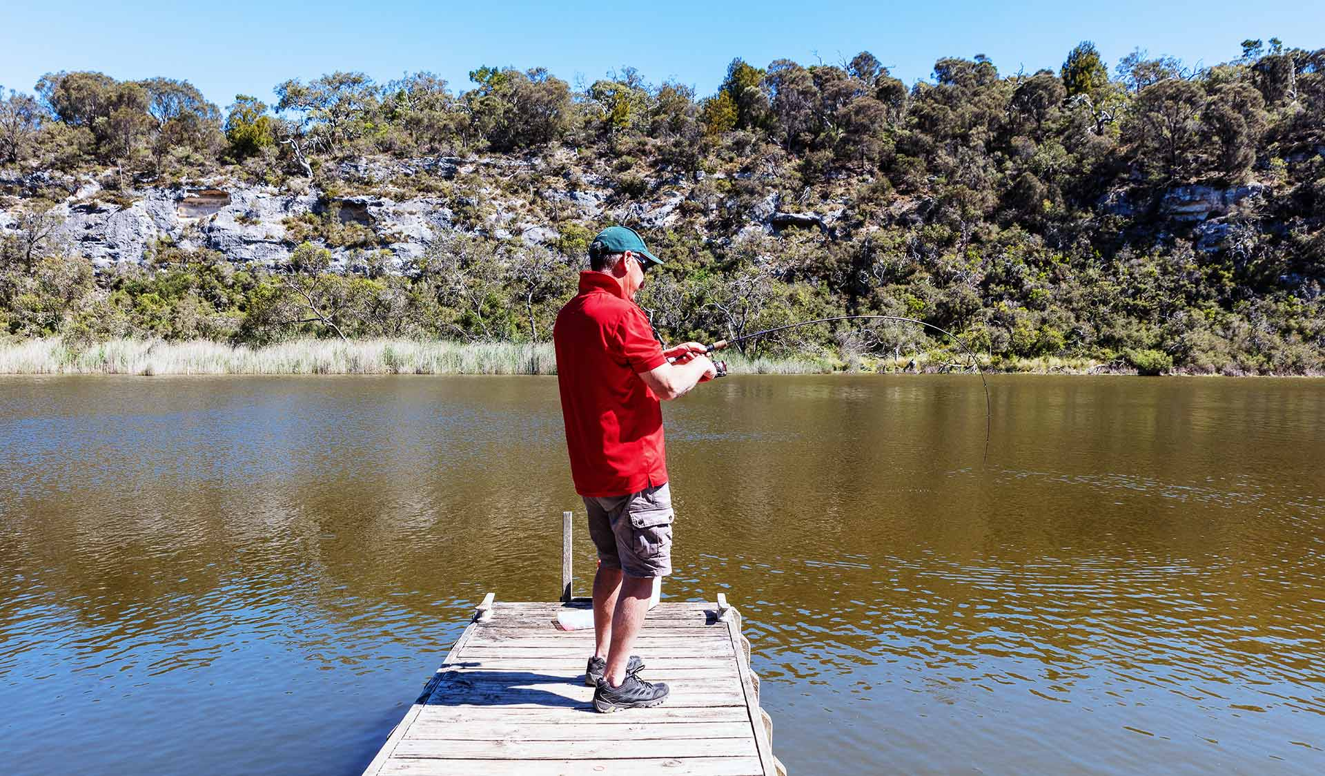 A man fishes from a jetty in the Glenelg River.
