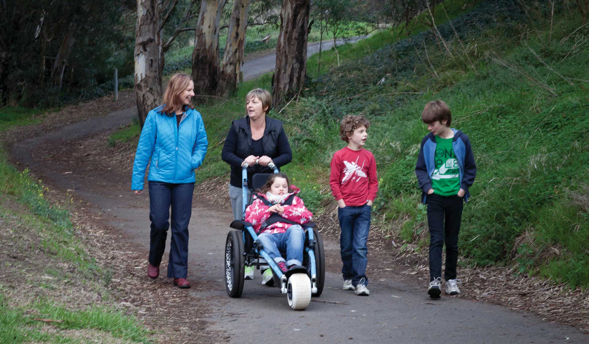 Two adults and three children, one of which is in a wheel chair, stroll along a path at Brimbank Park.