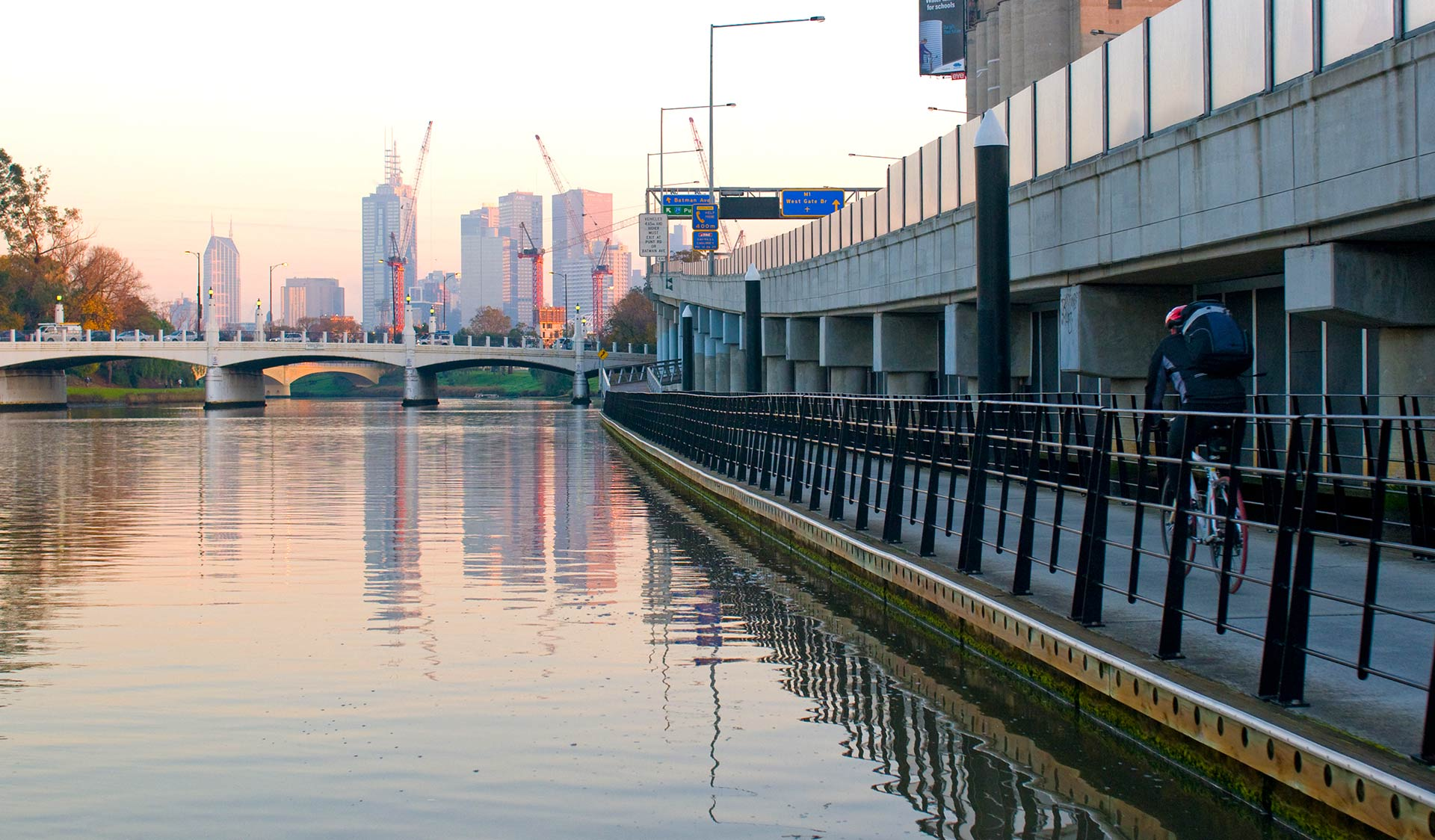 A cyclist follows the bike path along the Yarra River heading in to the Melbourne CBD at sun set.