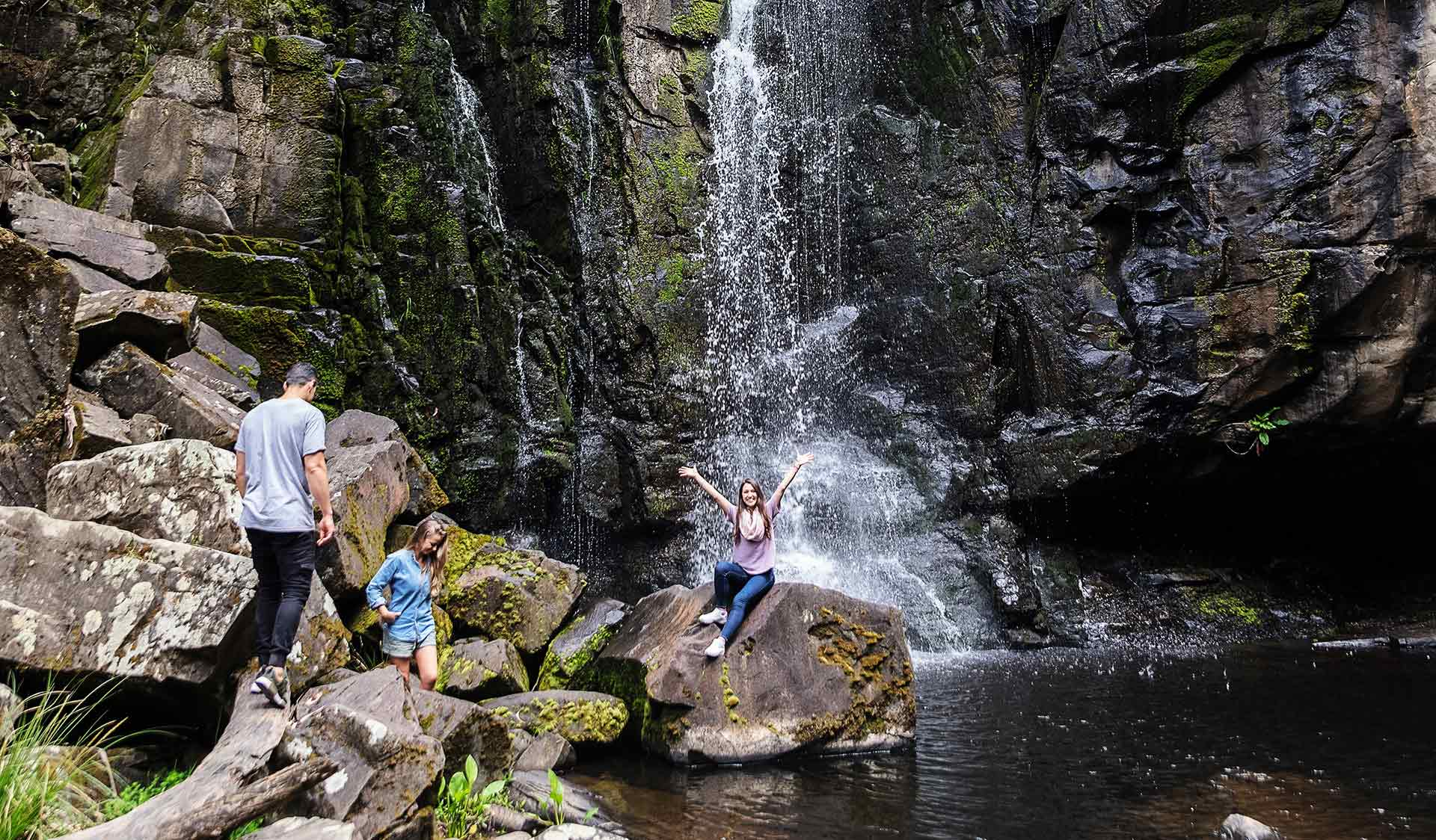 A women sitting on a rock in front of a waterfall calls out to her friends to join her.
