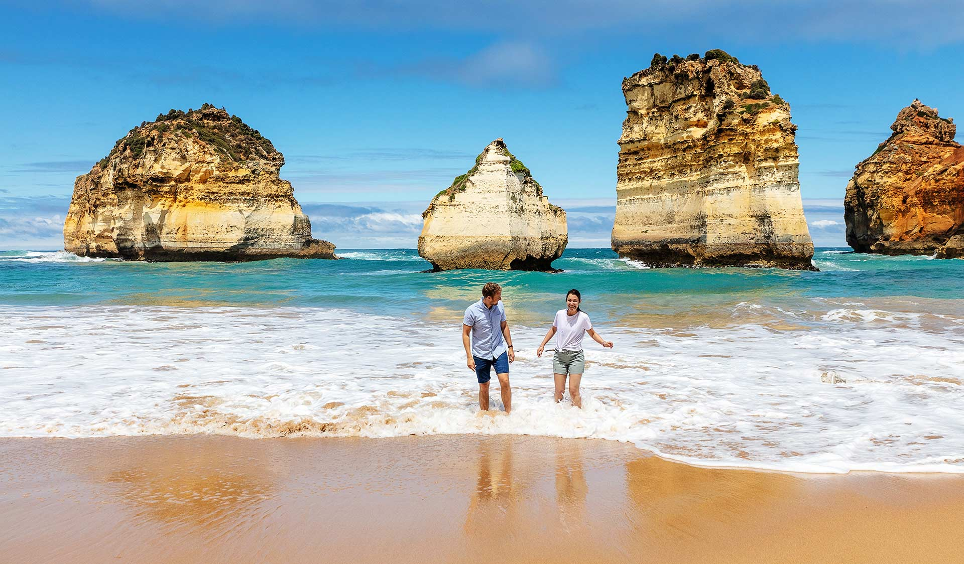 A man and woman play in shallow waters in front of the Twelve Apostles.