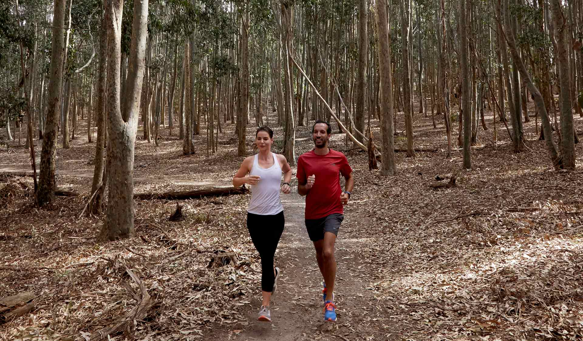 A couple run through the bush and leaves at Lysterfield Park.