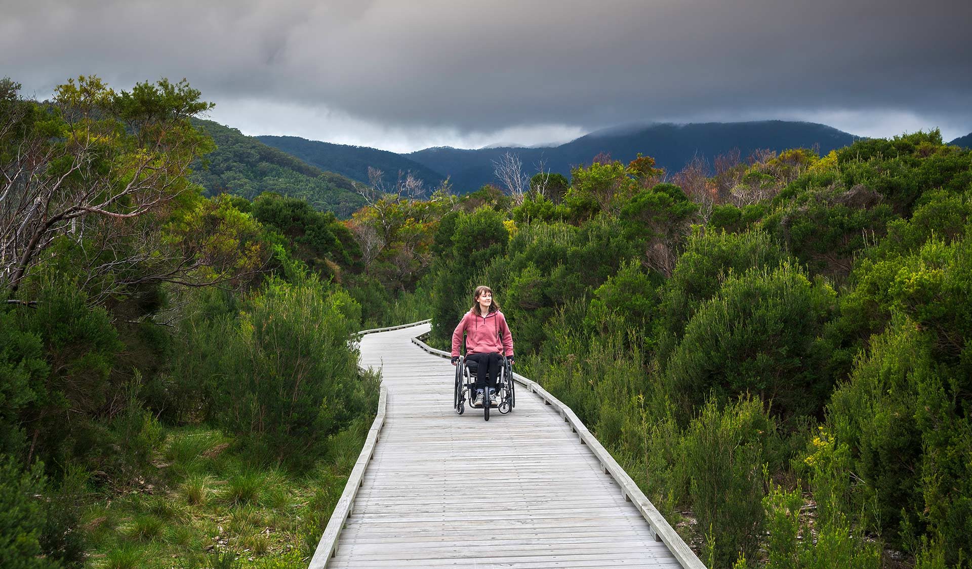 A women in a wheel chair explores Wilsons Promontory by board walk.