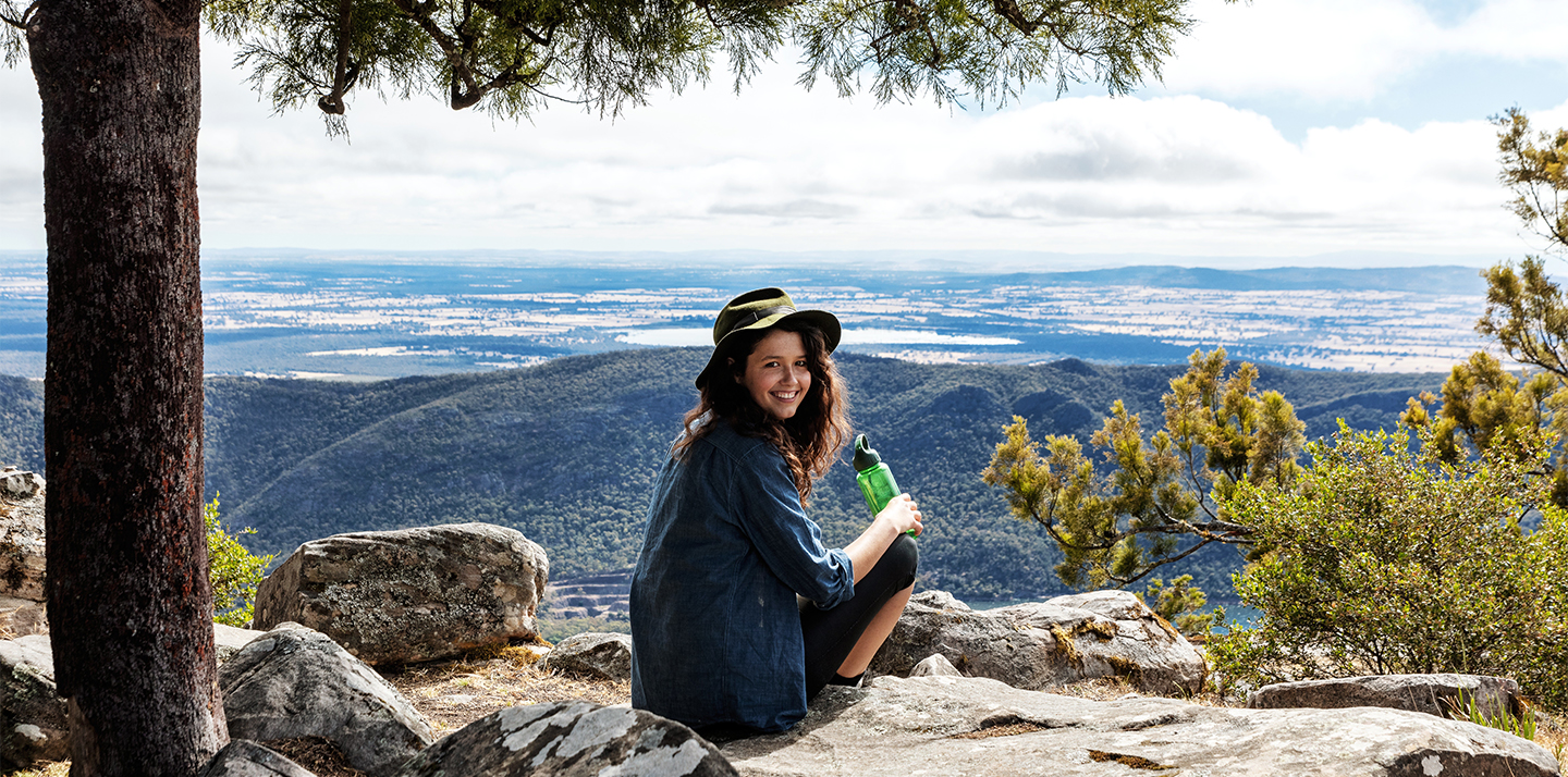 A smiling female park visitor wearing a hat and holding a water bottle, sitting in nature overlooking a view.