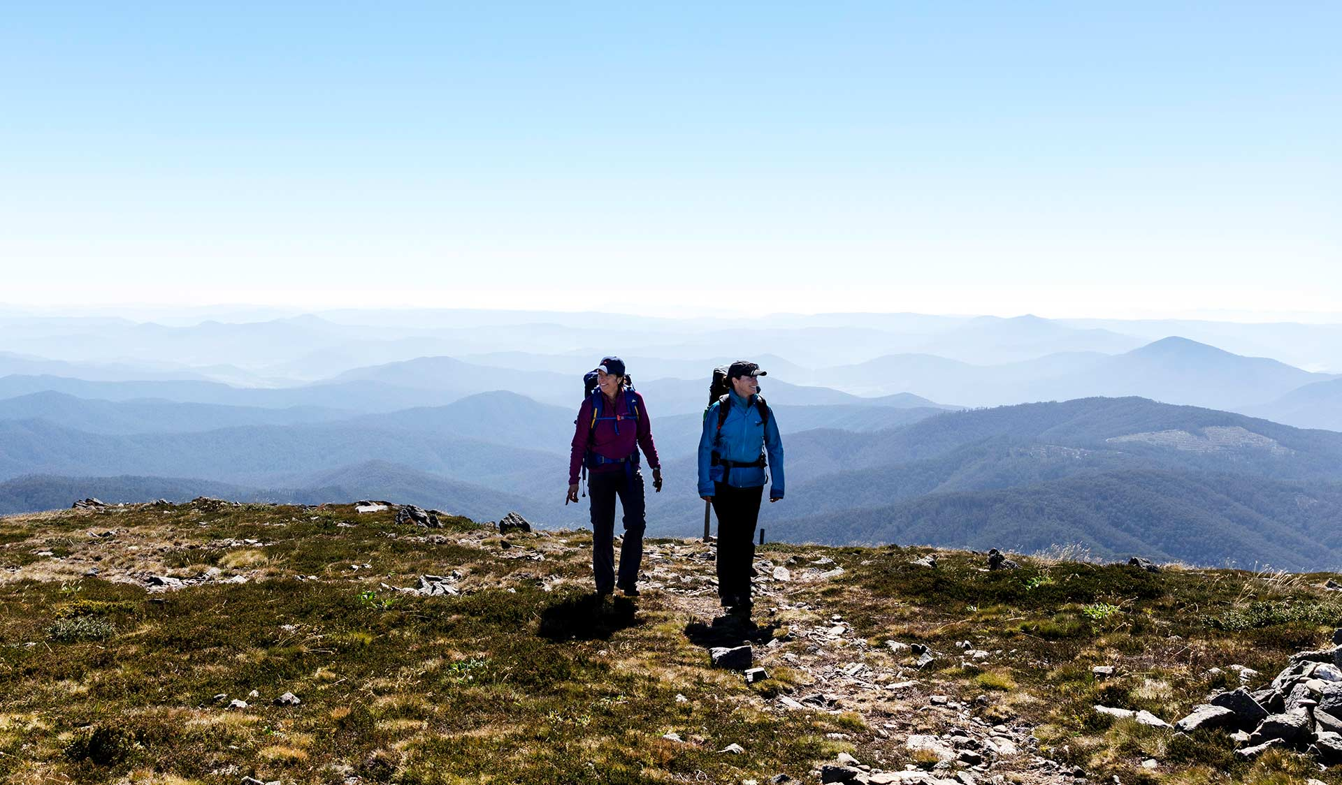 Two women hiking with a panoramic view of the mountains behind them at Alpine National Park