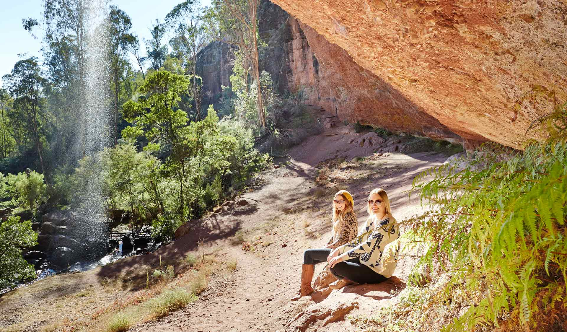 Two women sit beside the ephemeral Paradise Falls located near the headwaters of the King River in the Alpine National Park.
