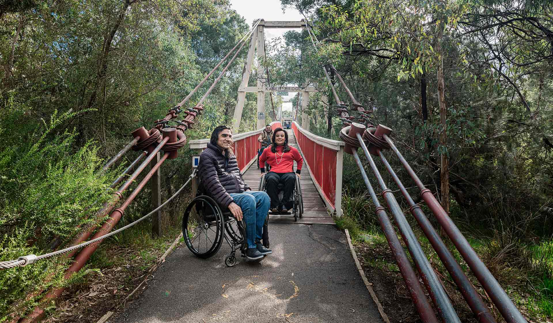 Man in wheelchair waits as his two friends cross accessible Kane's Bridge in Yarra Bend Park.