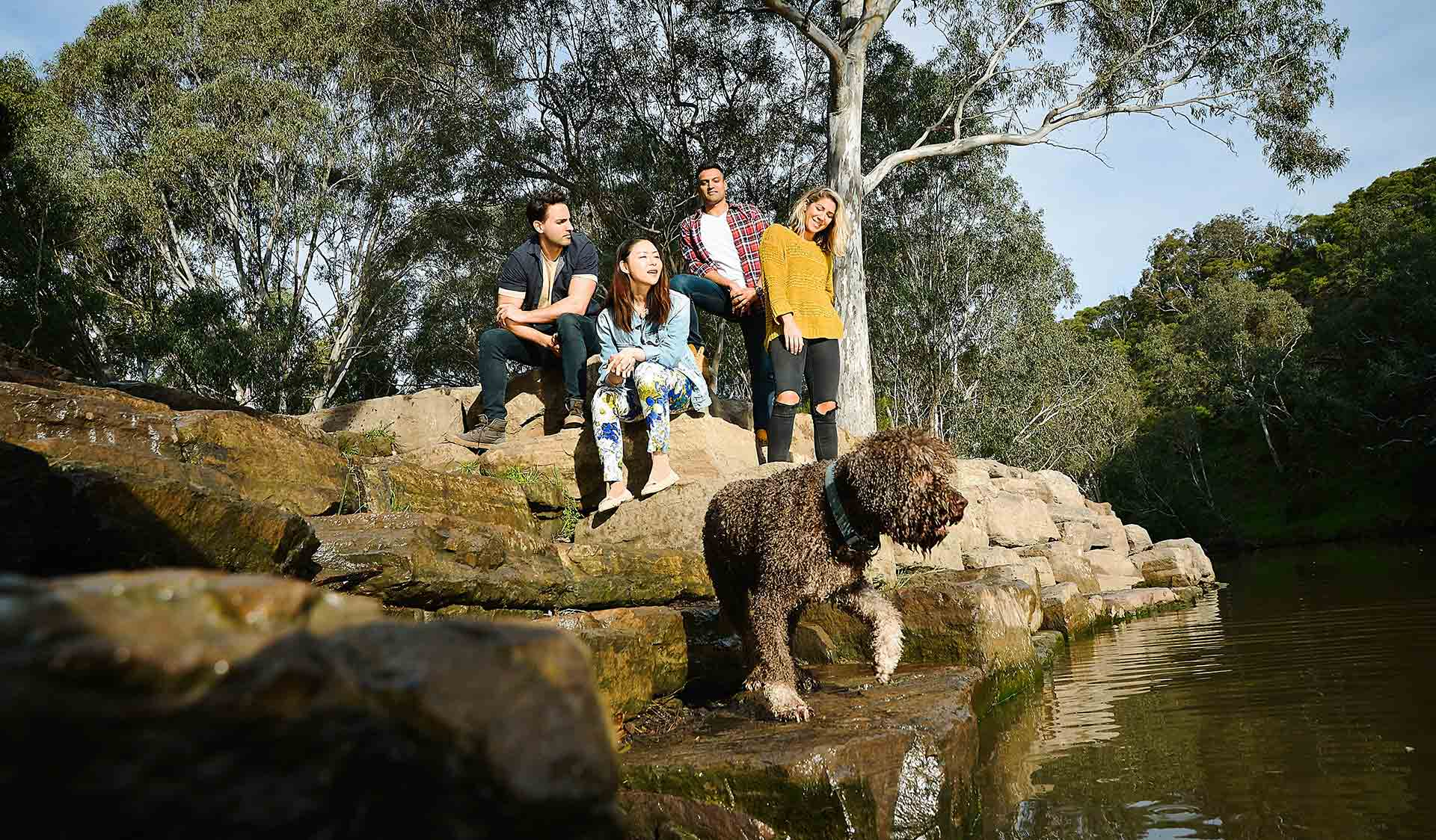 Four friends resting on rocks while watching their dog in front of them by the Yarra River