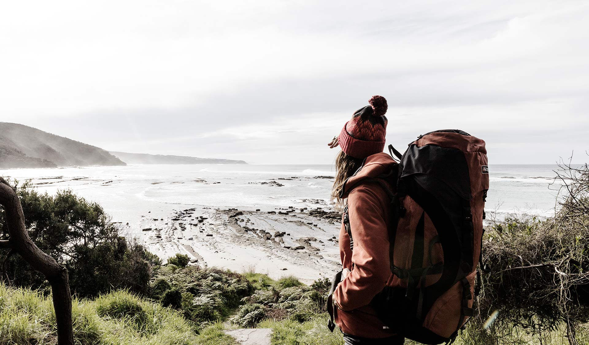 A woman with a large hiking pack takes in the view from Blanket Bay Campground.