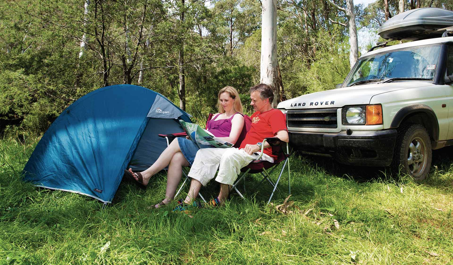 A couple sit and look at a map next to their tent and car.