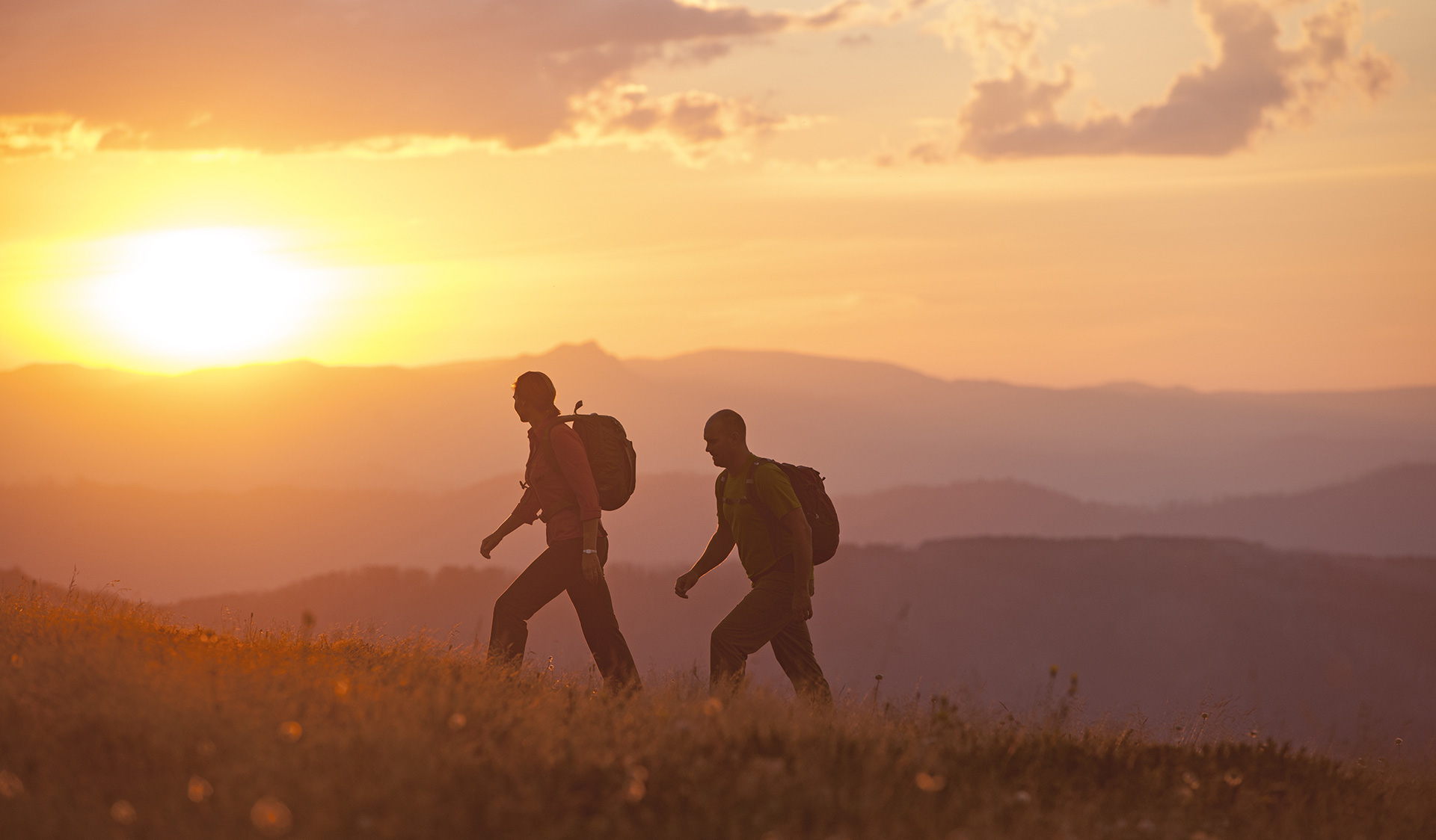 Two walkers head across the Razorback near Mt Feathertop at Sunset.