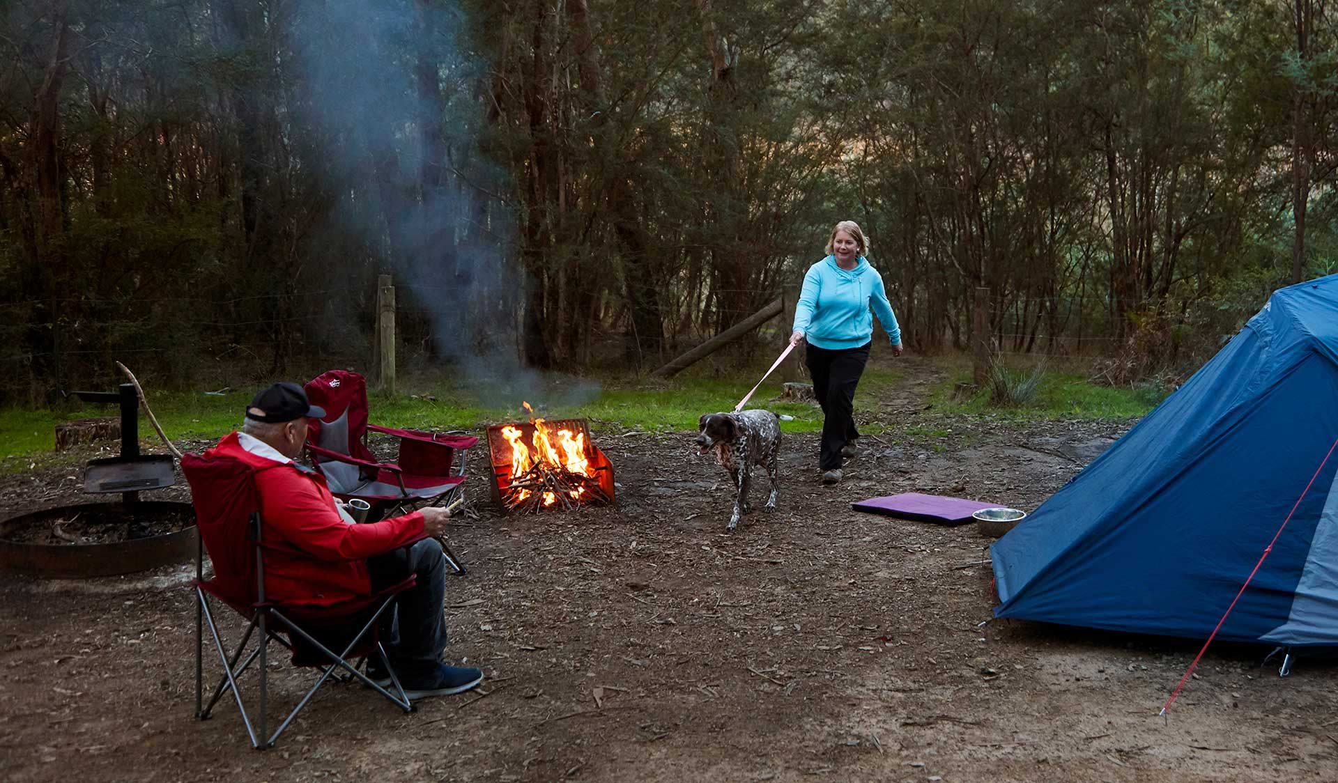A couple and their dog camp around a fire at Jerusalem Creek camp ground.