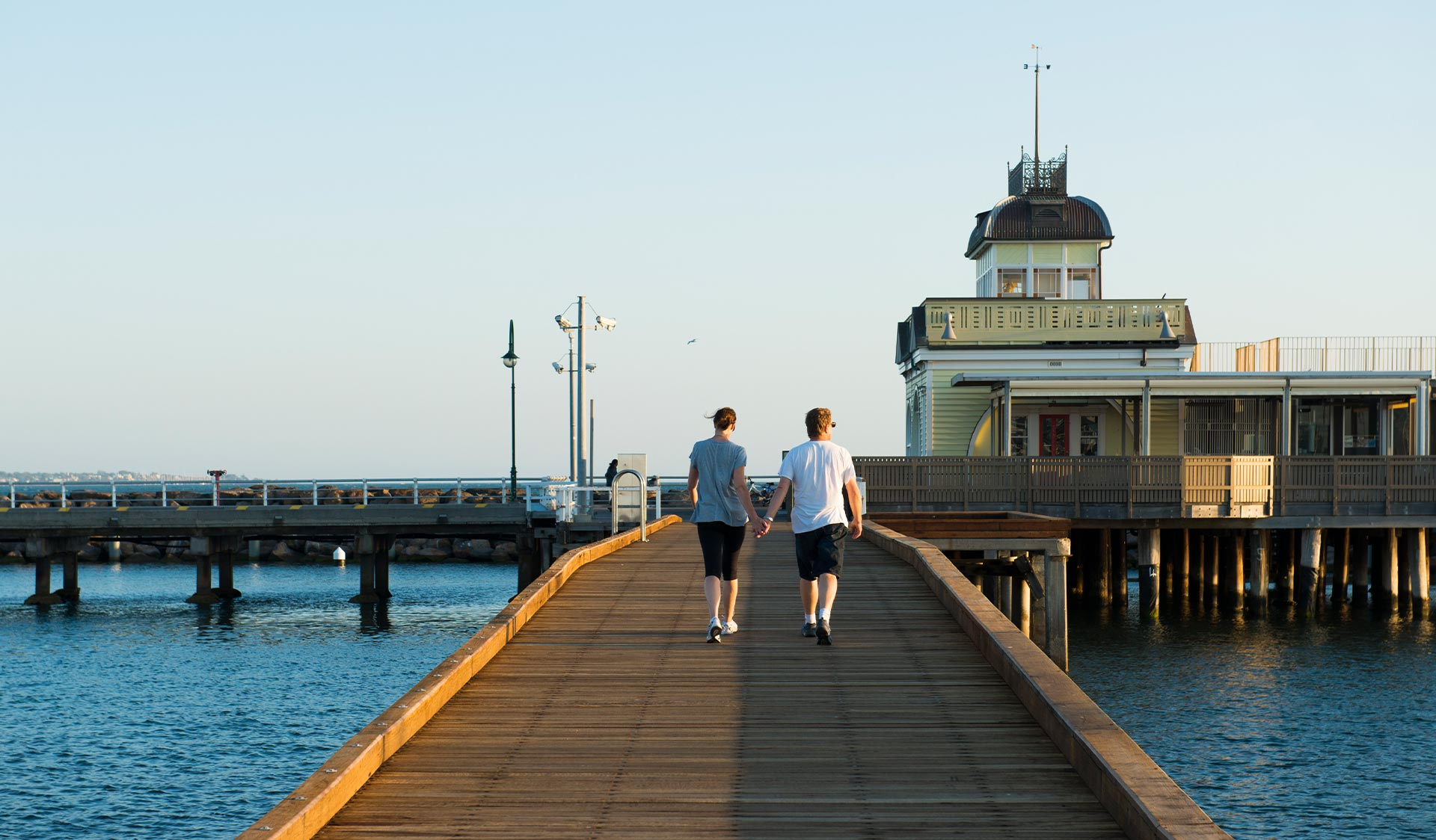 A couple walks along St Kilda Pier