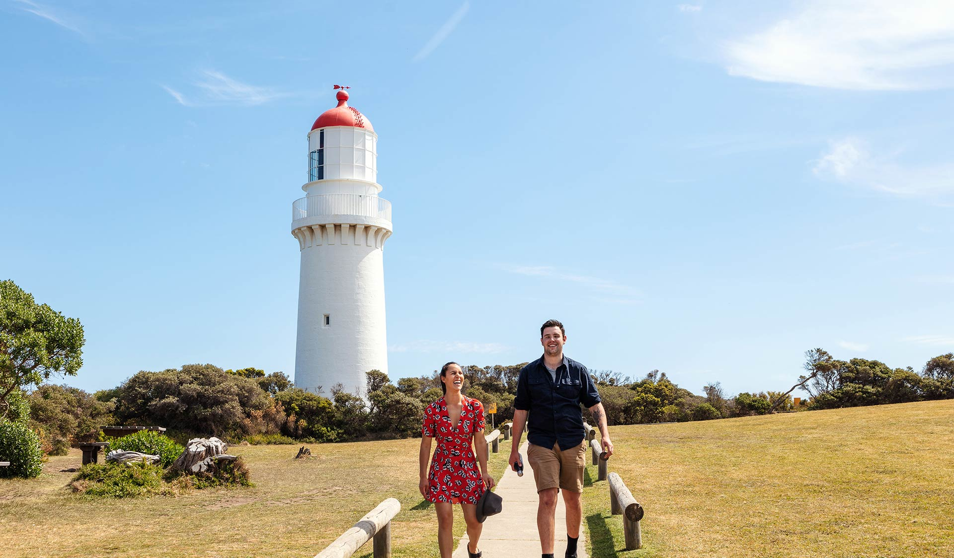 A couple walk down the track and away from the Lighthouse at Cape Schank on the Mornington Peninsula.