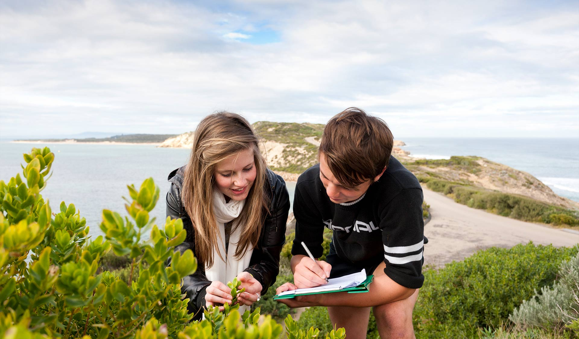 Two teenage children studying plants and making notes