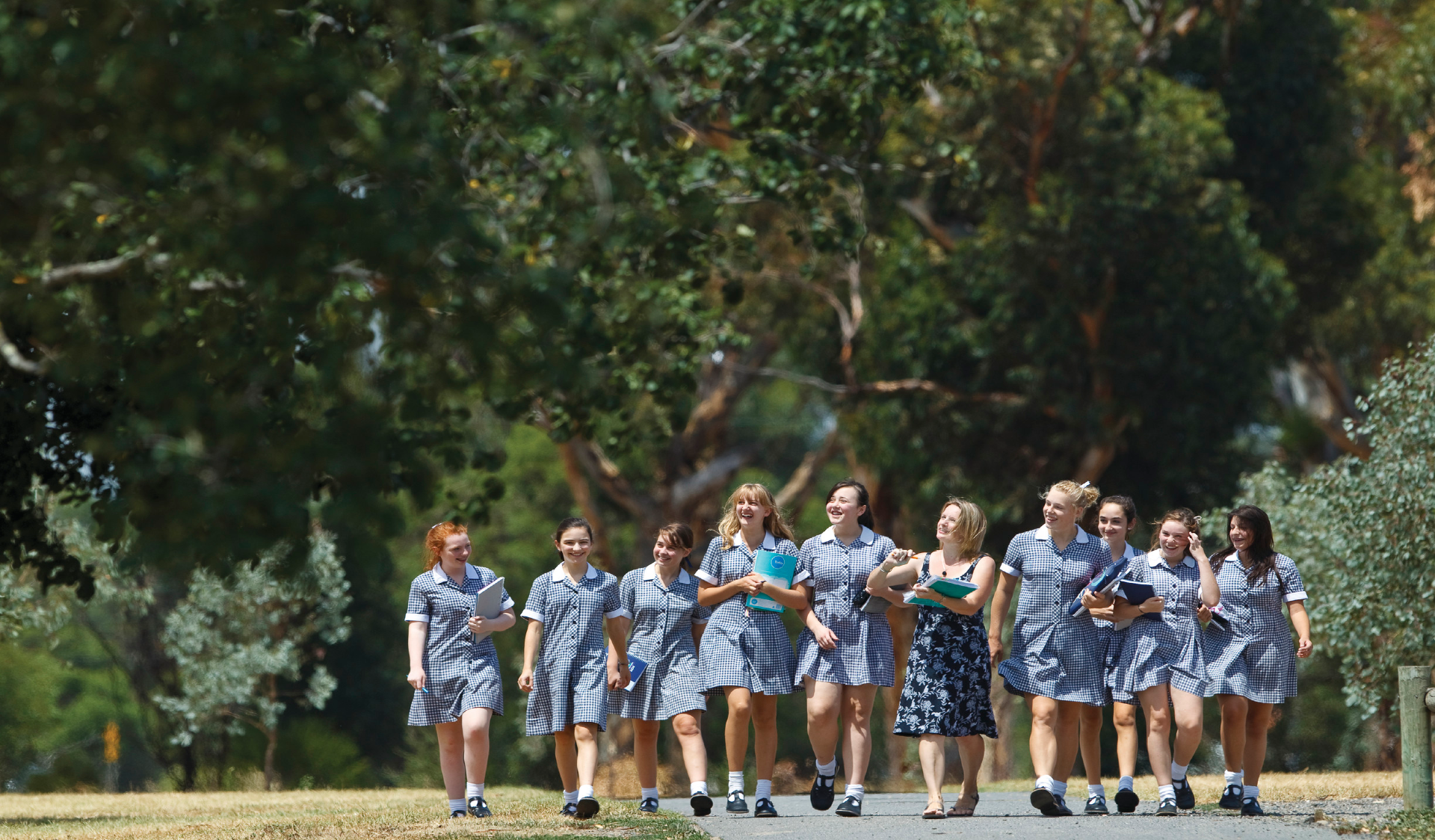 School students walking with teacher through an urban park on an excursion