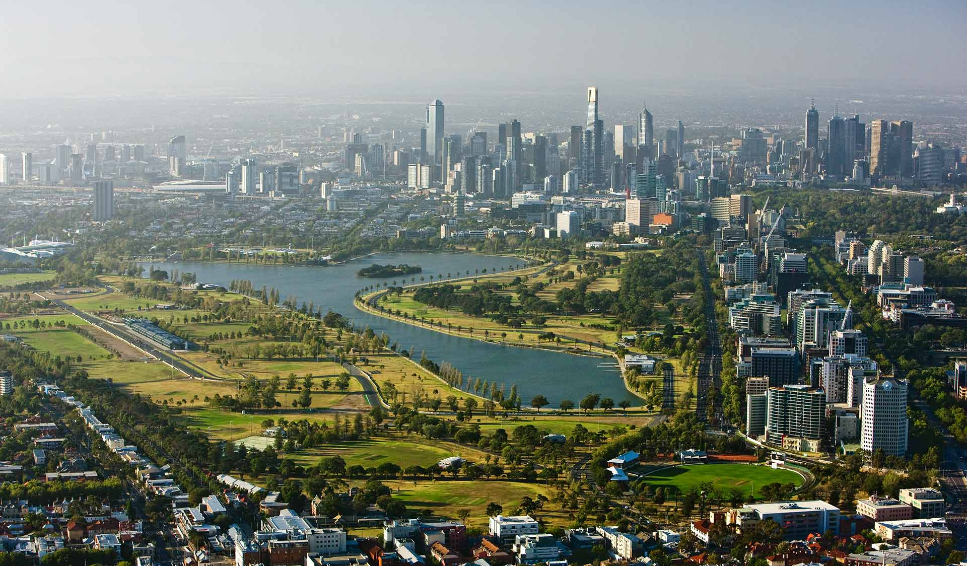 An aerial view of Albert Park Lake with the Melbourne CBD skyline in the background.