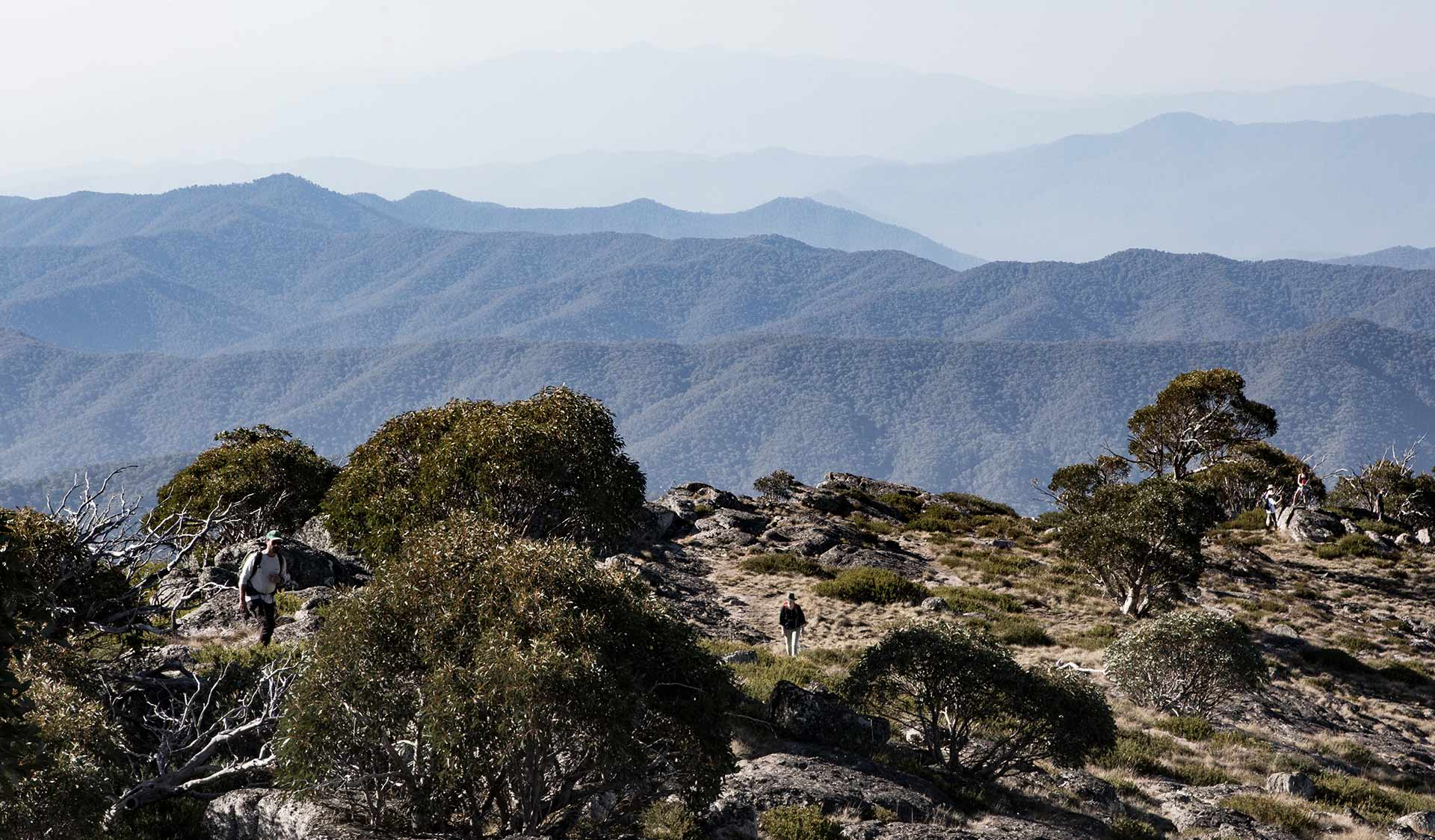 A woman hikes to the top of Mt Cobbler with spectacular views of the High Country in the background.