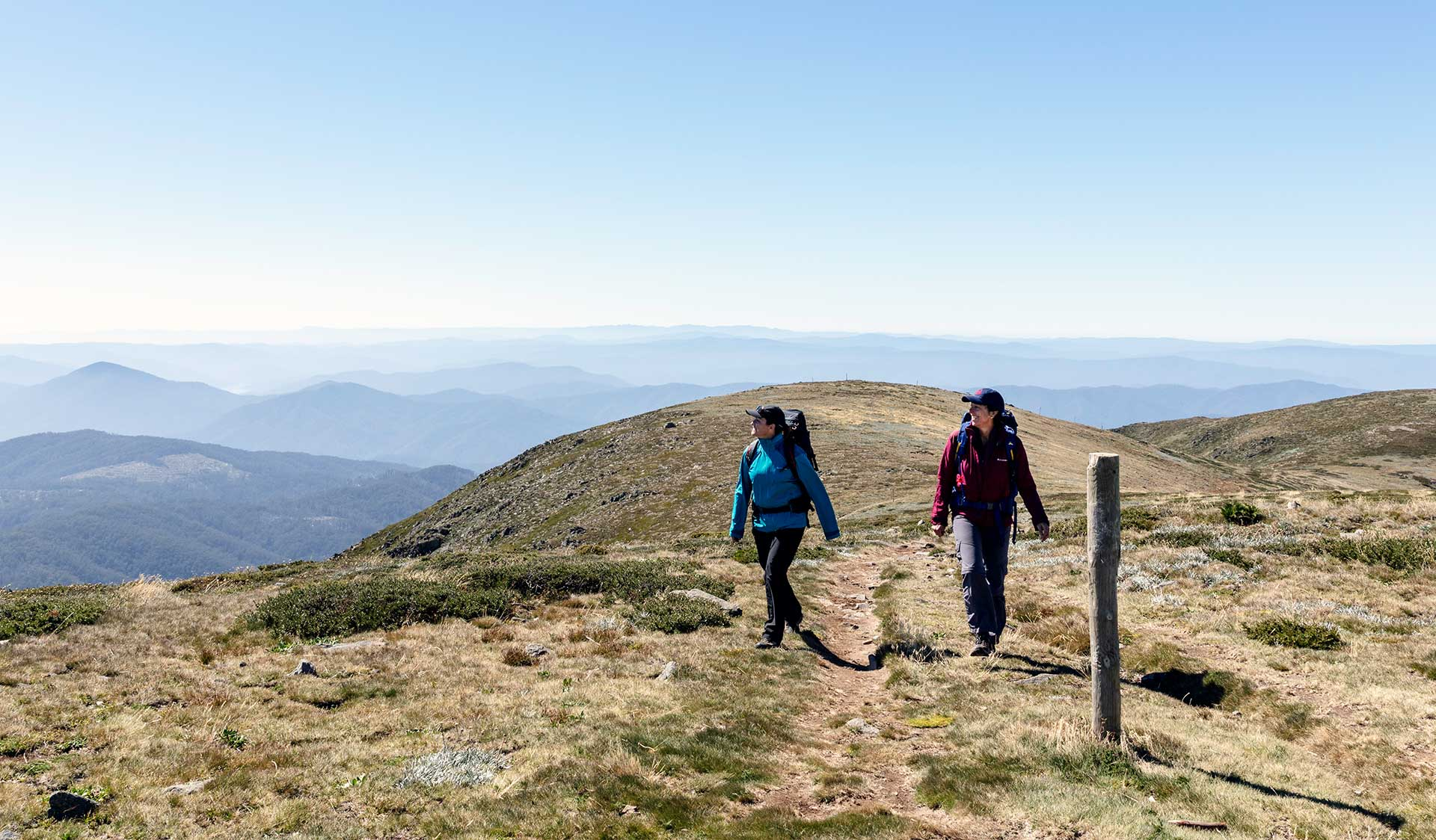 Two women walk towards the summit of Mt Bogong in the Alpine National Park.