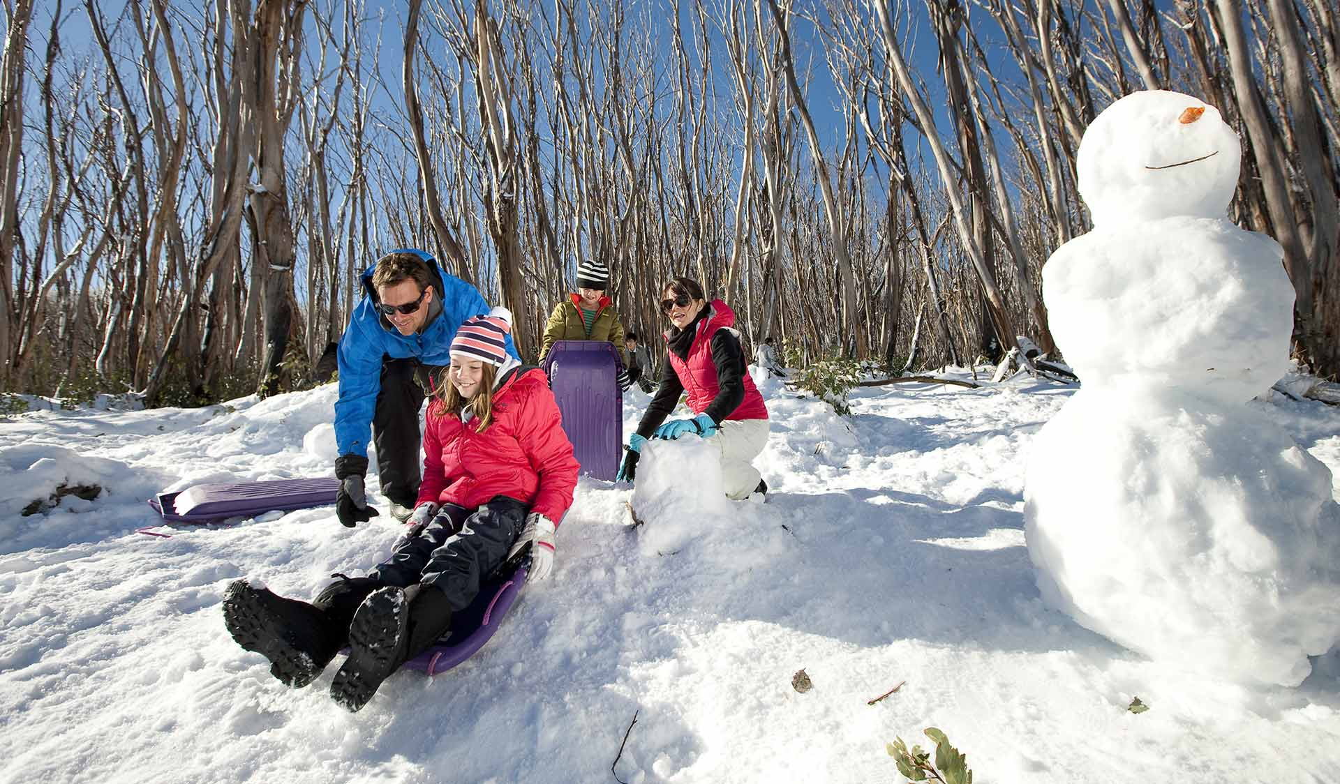 A family plays in the snow at Mt St-Gwinear in the Baw Baw National Park.