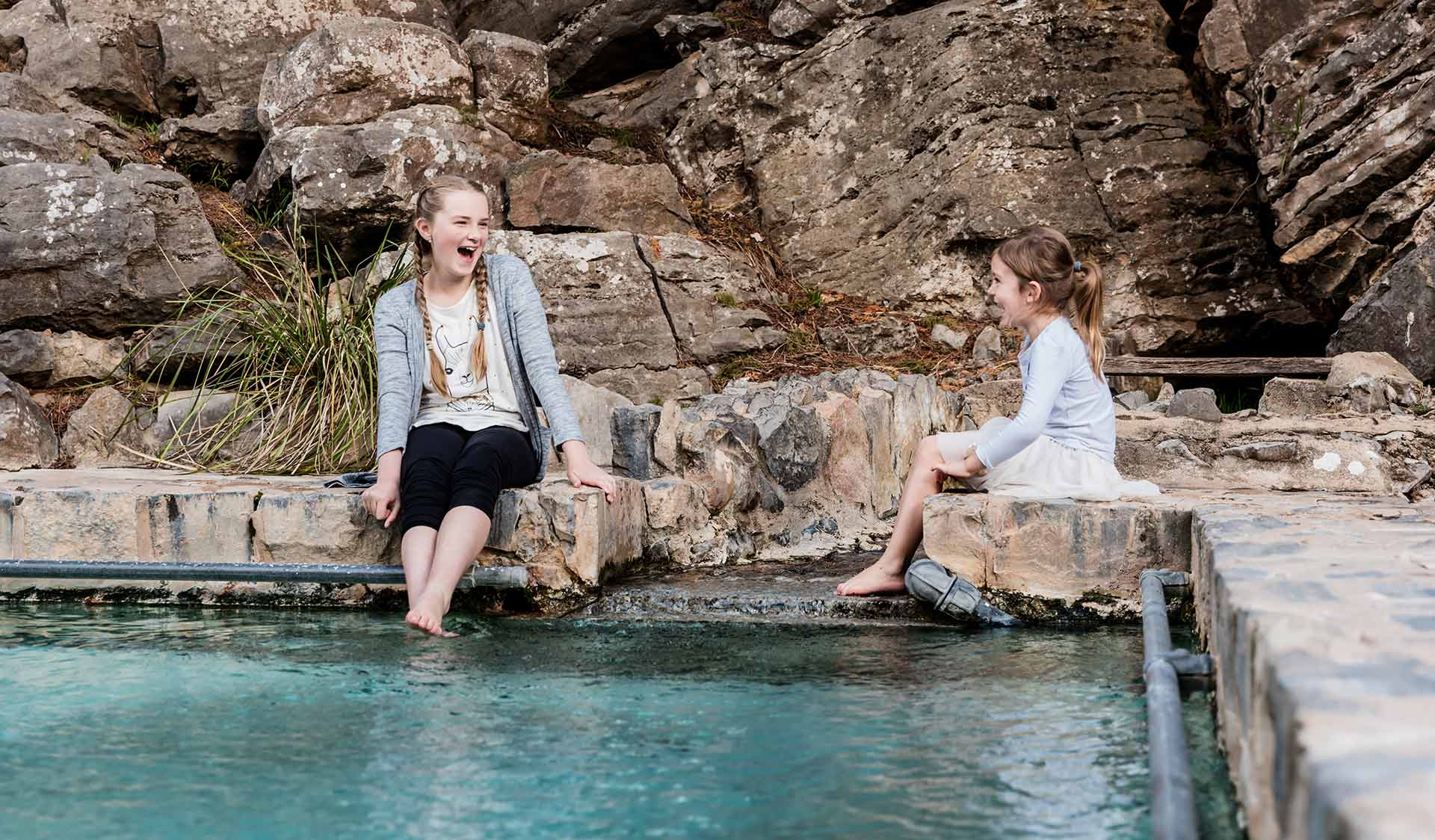 Two young girls sit on the edge of the natural spring swimming pool at Buchan Caves and dangle their feet into the water.