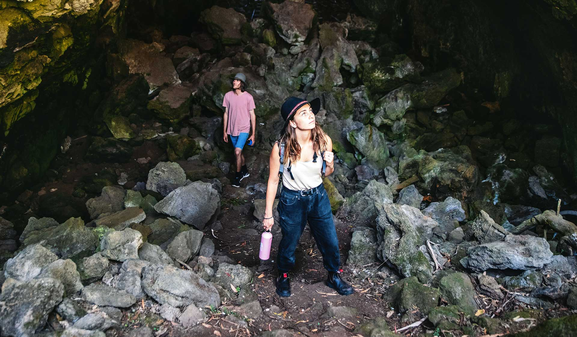 A young couple walk through a cave in Budj Bim National Park