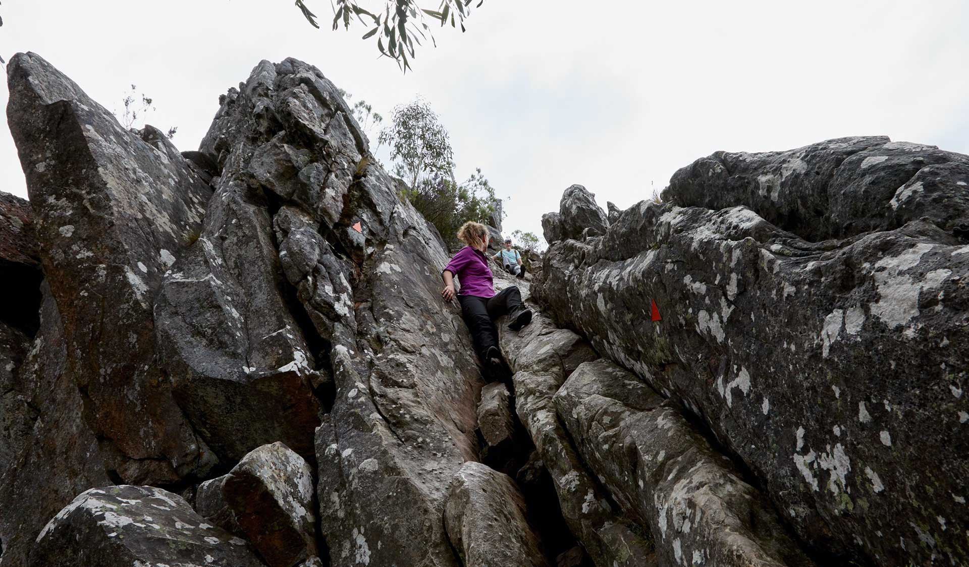 A woman in a purple shirt scrambles up through rocky terrain along the path.