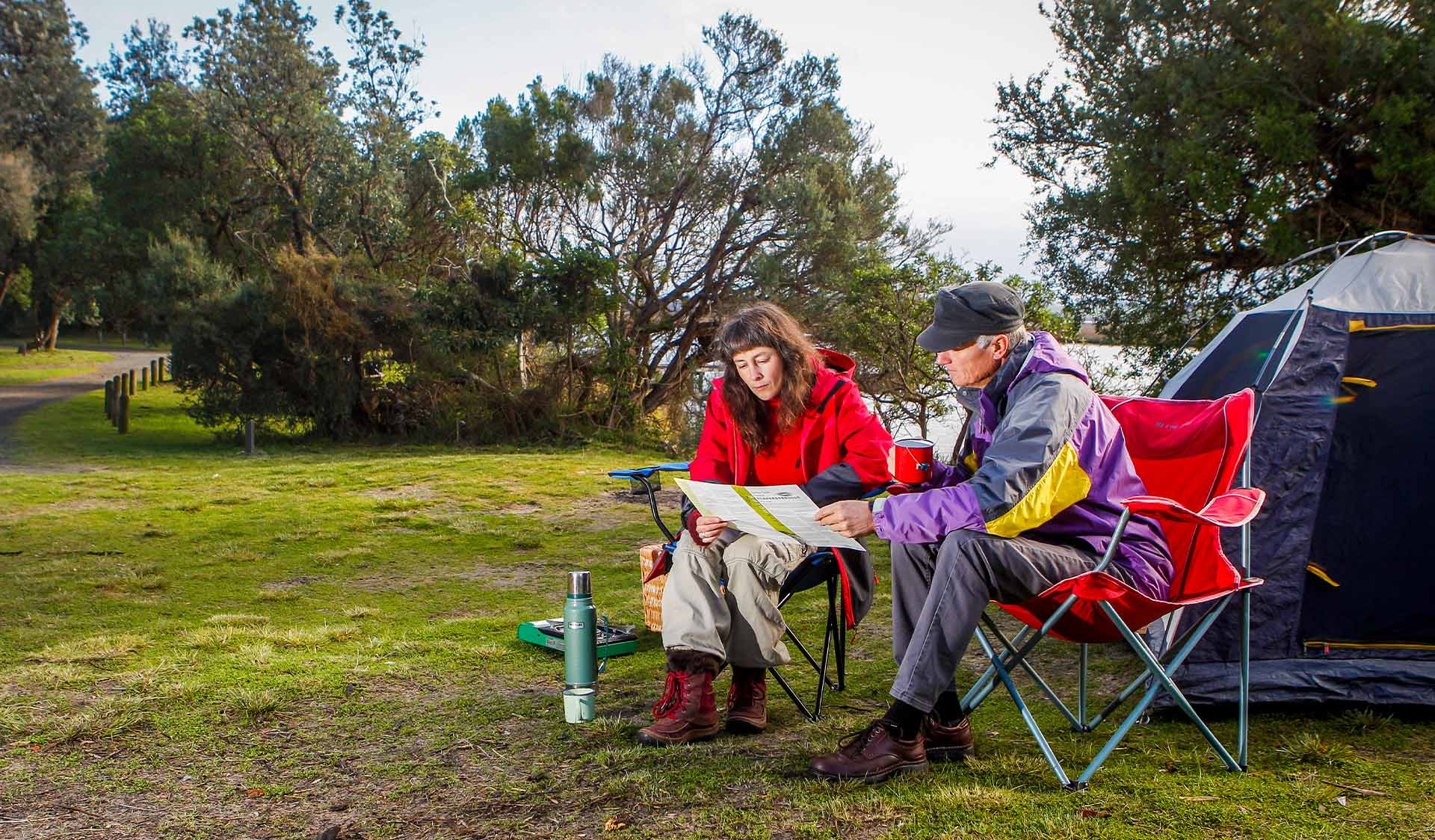 A couple sit in front of their tent at Corringle Foreshore Reserve.