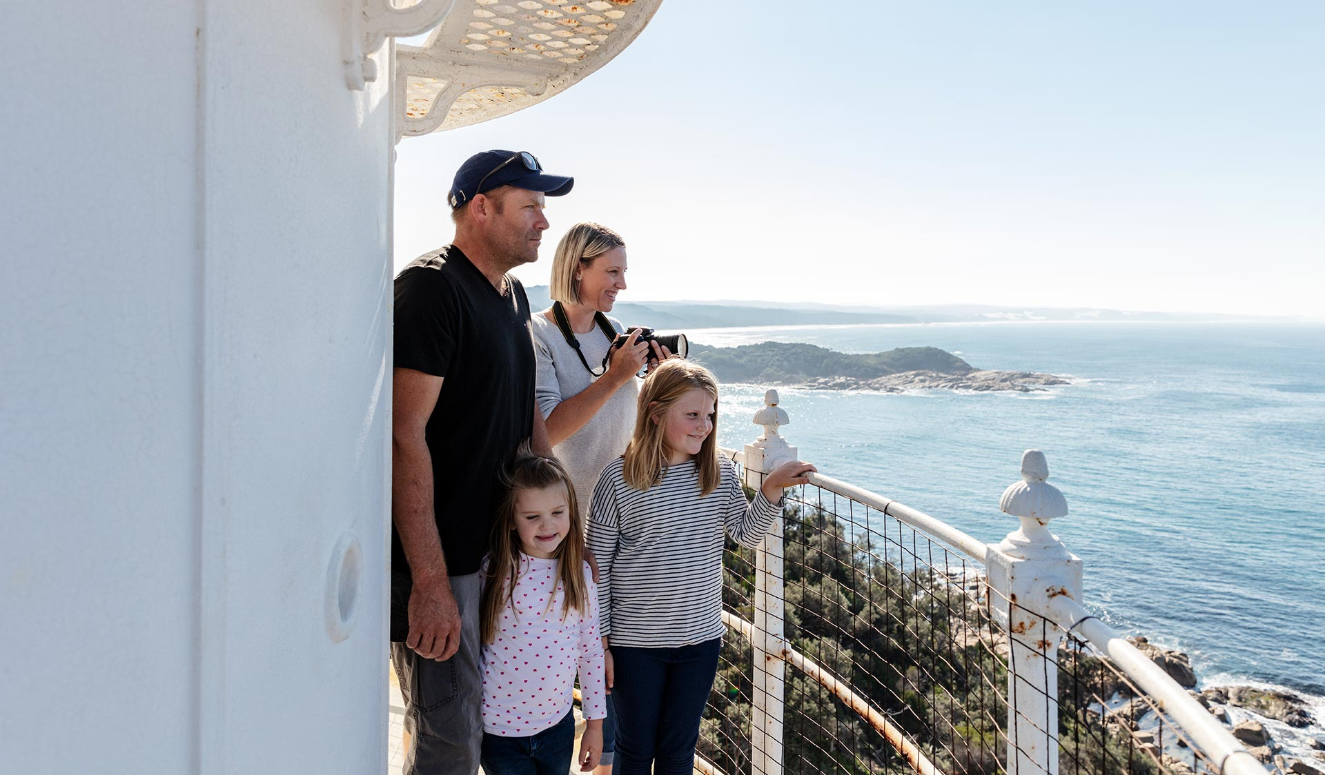 A mother, father and their two young daughts gaze out at the sea from the lookout point of the lighthouse.