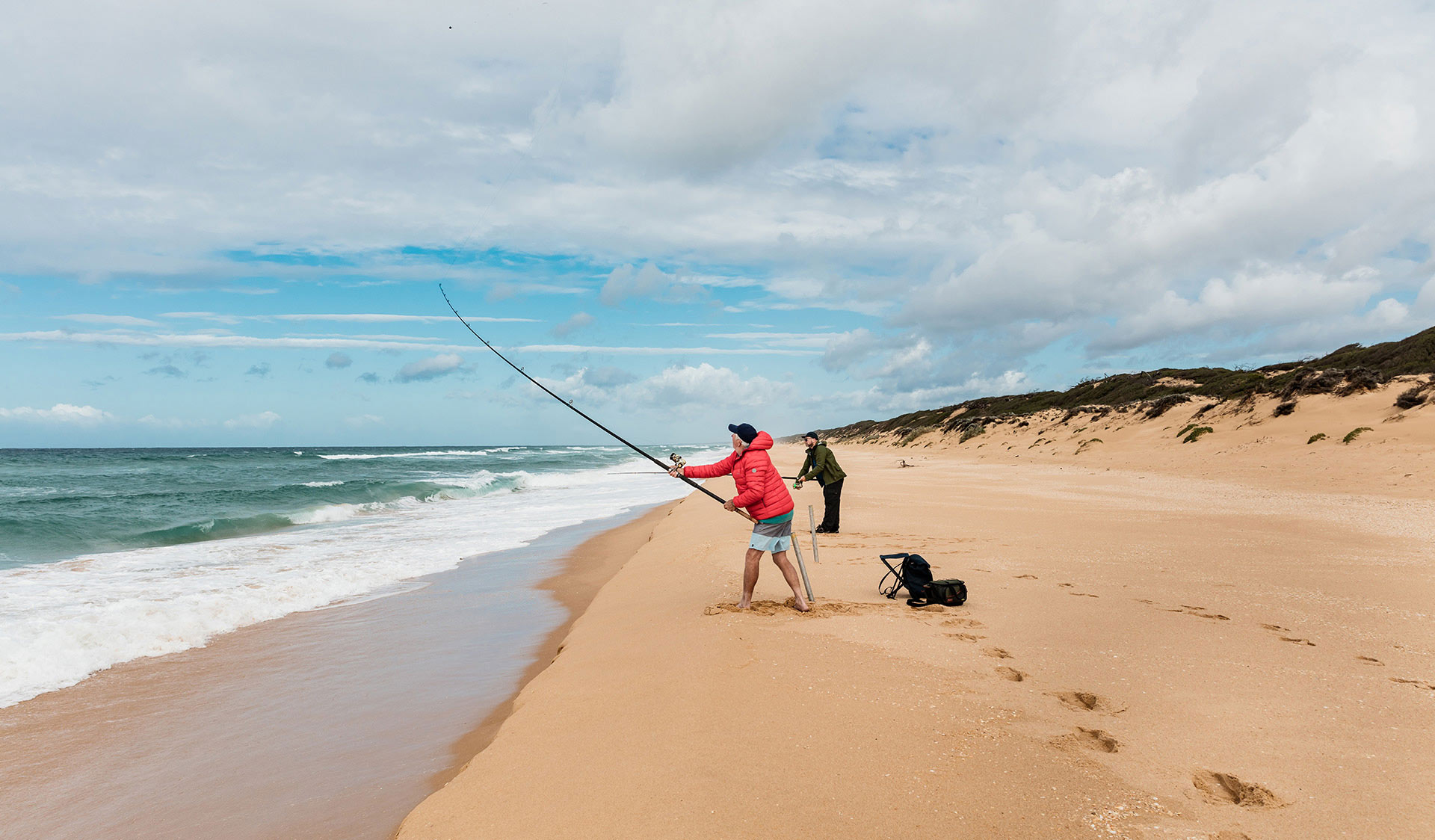 Two men fish along 90 mile beach.