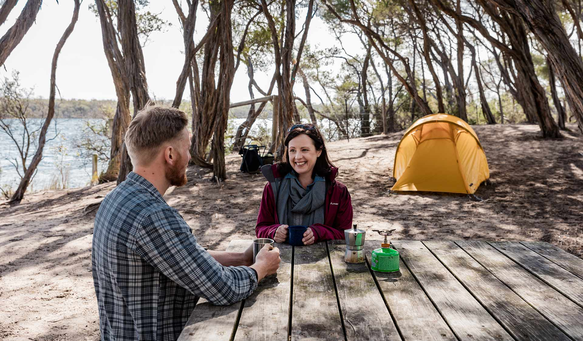 A woman enjoys a cup of tea while sat at a picnic table infront of her tent at Bunga Arm Campsite in the Gippsland Lakes.
