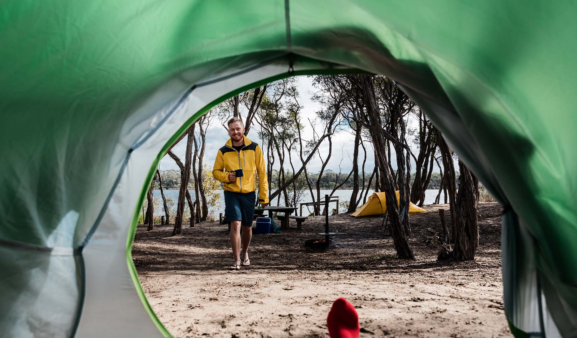A man in a yellow jacket holding a cup of tea walks towards his partner in a tent