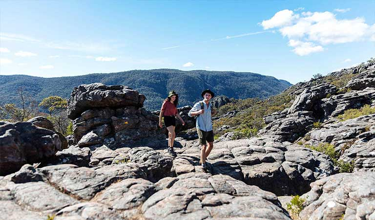 A young couple walks up through ancient lava flows to Sundial Peak in the Central Grampians