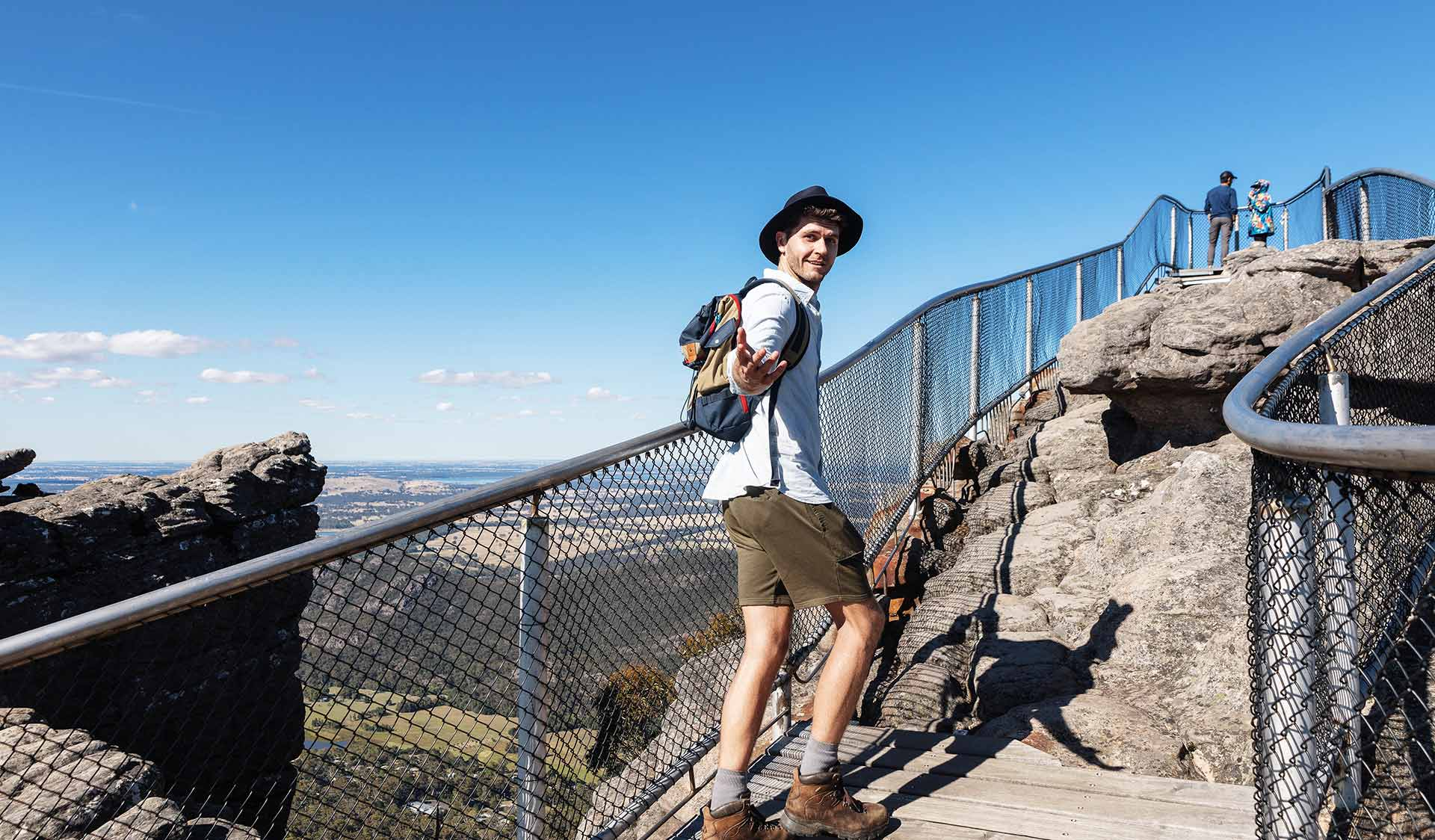 A young man offers his hand to his walking partner at the summit of The Pinnacle in the Grampians National Park.