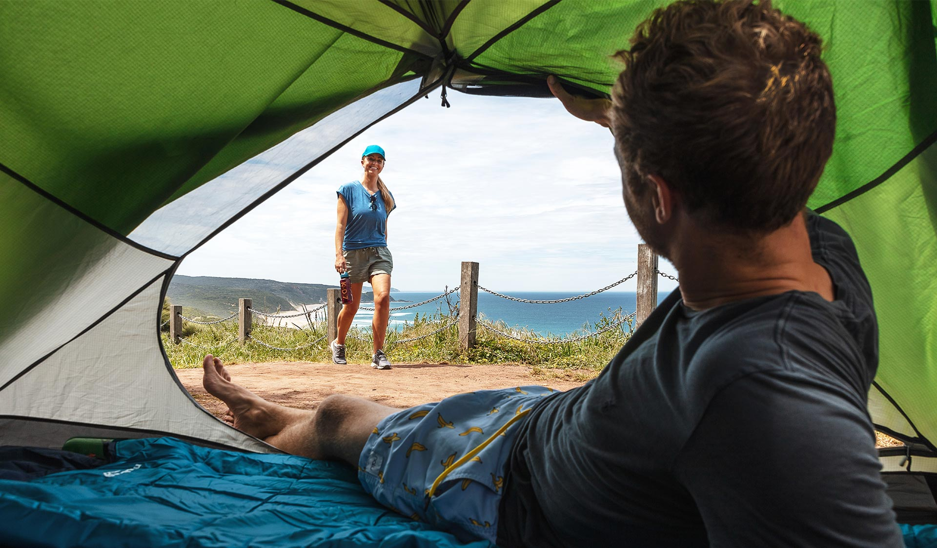 A man looks out of his tent towards his partner walking towards him with the coast in the background at Johanna Beach in the Great Otway National Park.