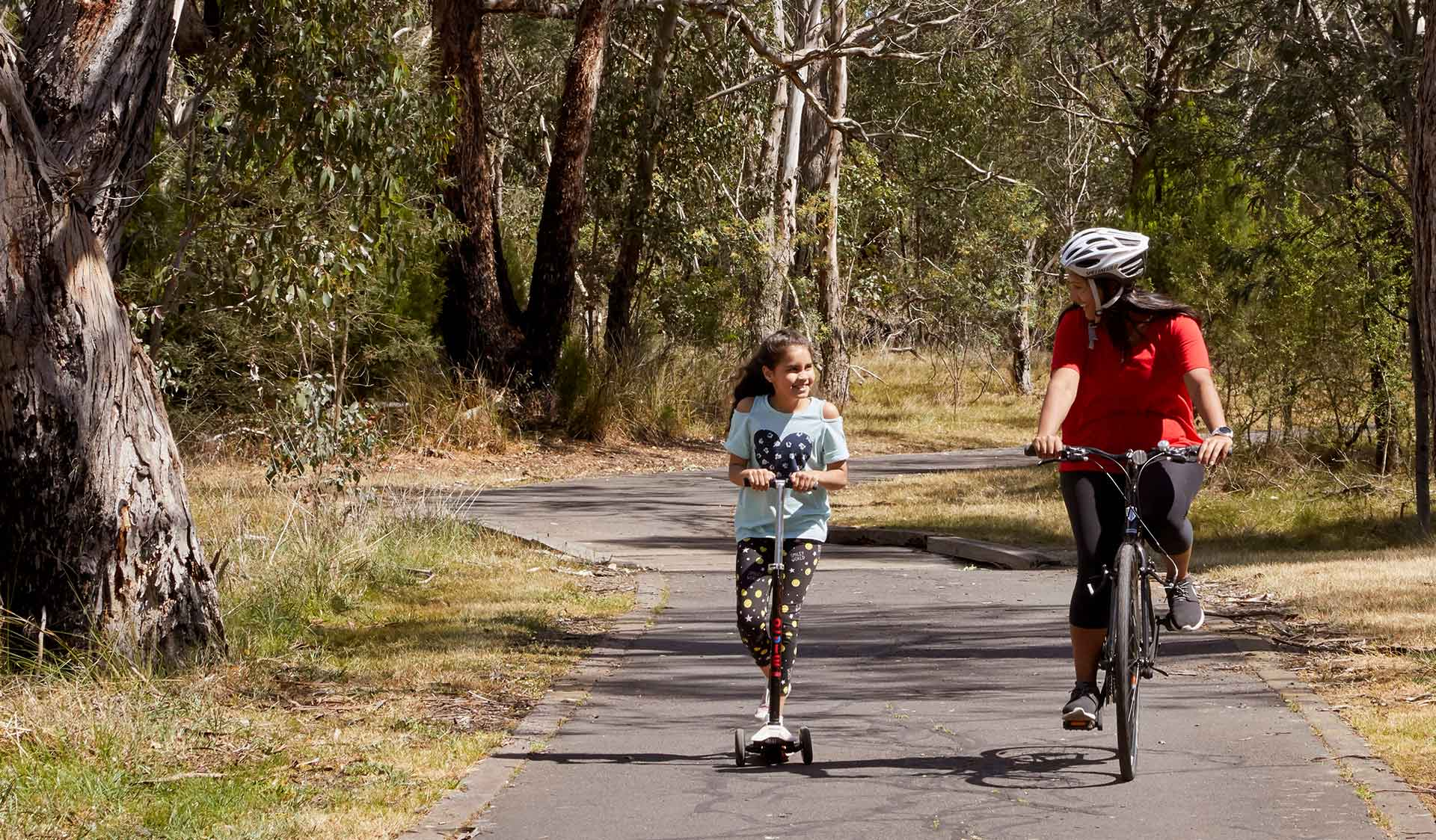 A woman riding a bike alongside a young girl on a scooter