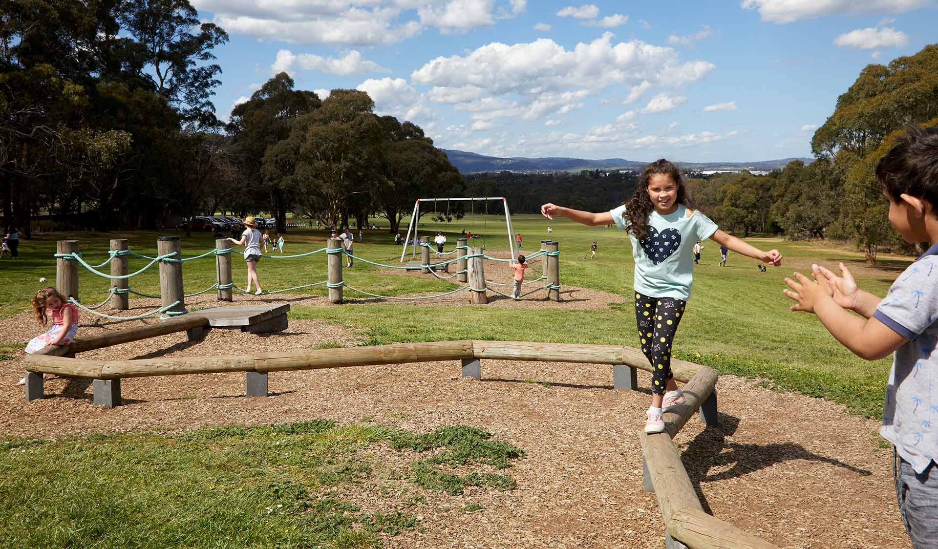 A young girl walking on a winding balance beam with children and families playing in the background at Yabby Hill Playscape