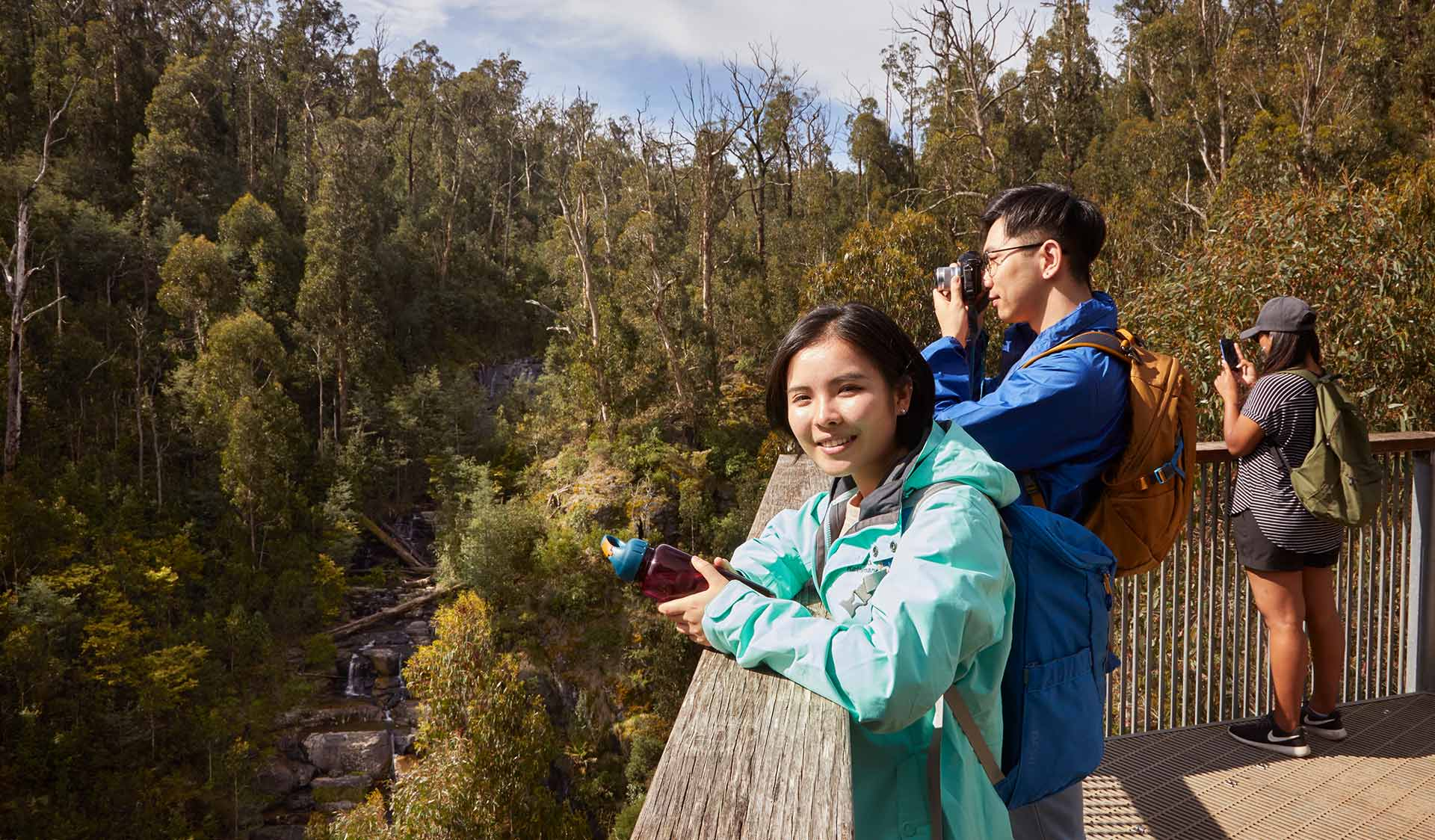A husband and wife stop to take a photo of Masons Falls from the lookout.