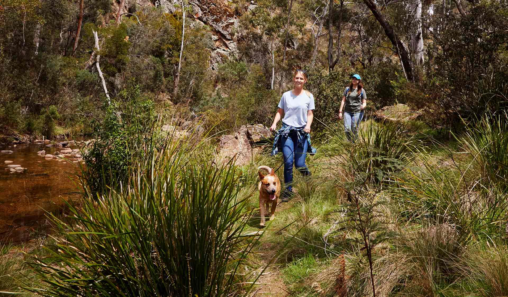 Two women walk an Australian Cattle Dog alongside a rocky creek.
