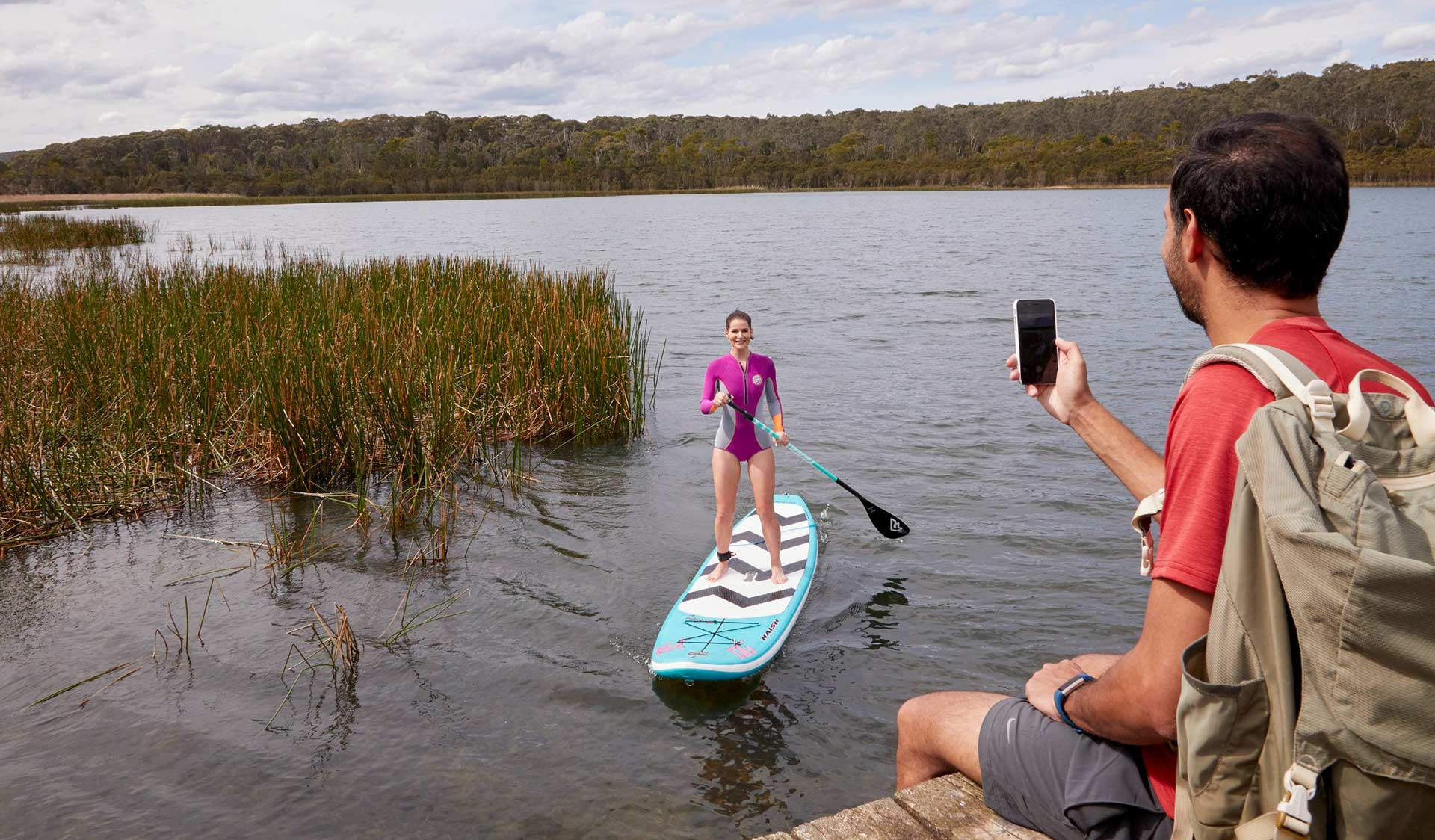 A man takes a photo from the bank of his partner on a stand-up paddle board on Lysterfield Lake.