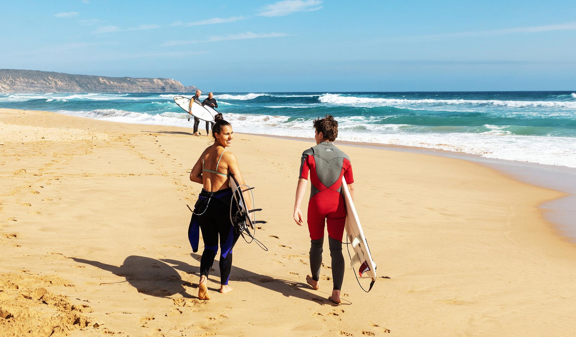 A man in a red wetsuit and a women with the top half of her wetsuit undone follow two men in to the surf on the Morning Peninsula.