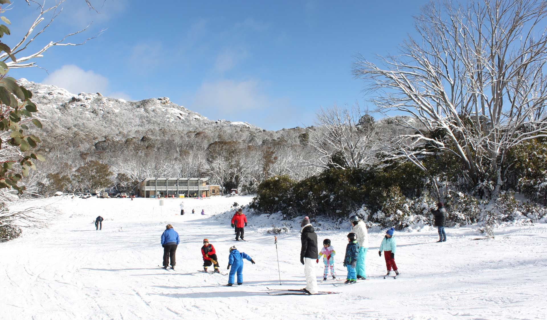 A family take a cross country skiing lesson at Dingo Dell at Mount Buffalo National Park