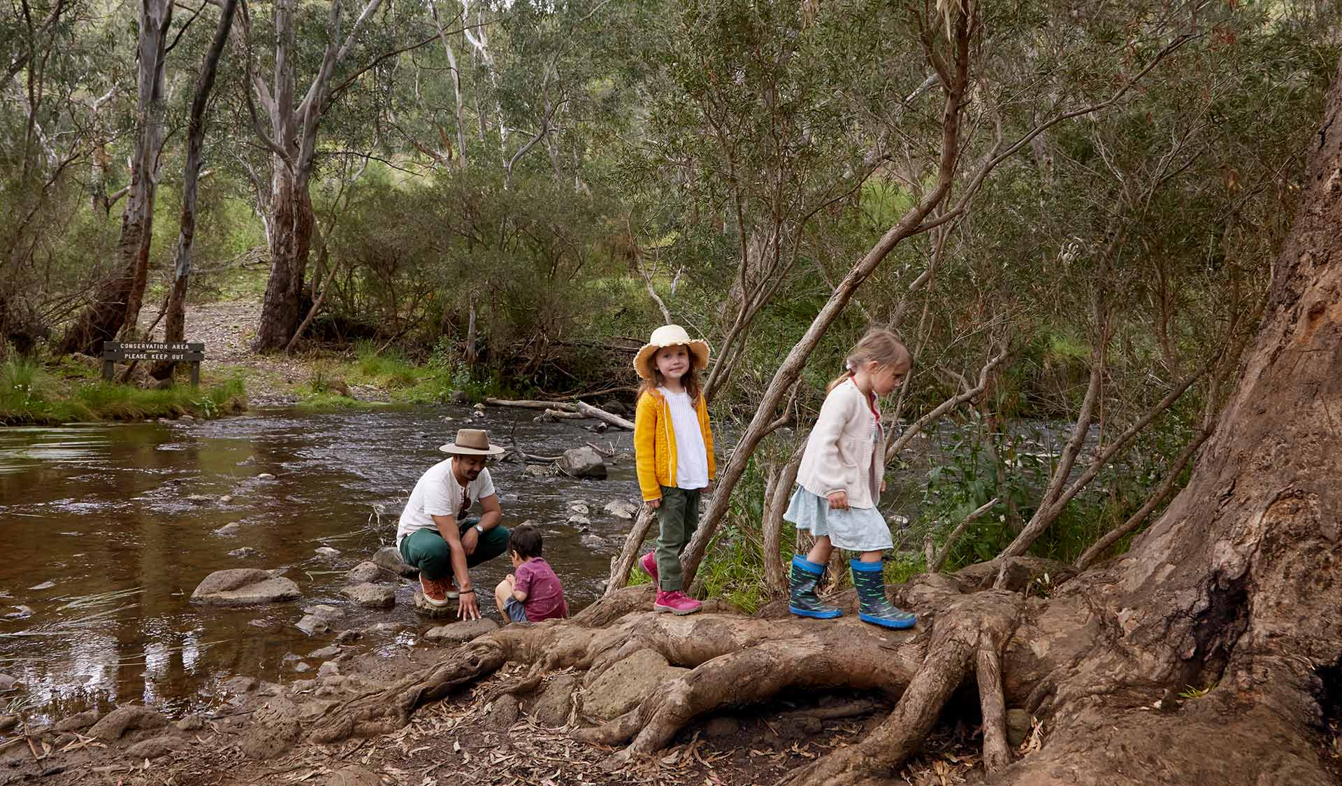 Three small children and a father cross a creek.